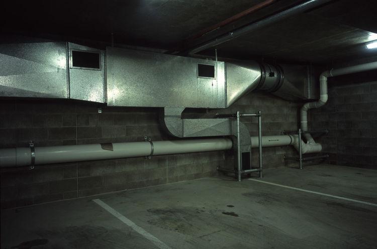 ducting in an underground carpark Breeze Block Carpark Concrete Ducting Empty Enclosed Exausted Exhaust Floursecent Light Fumes Unstock Vent Ventilation Ventilator