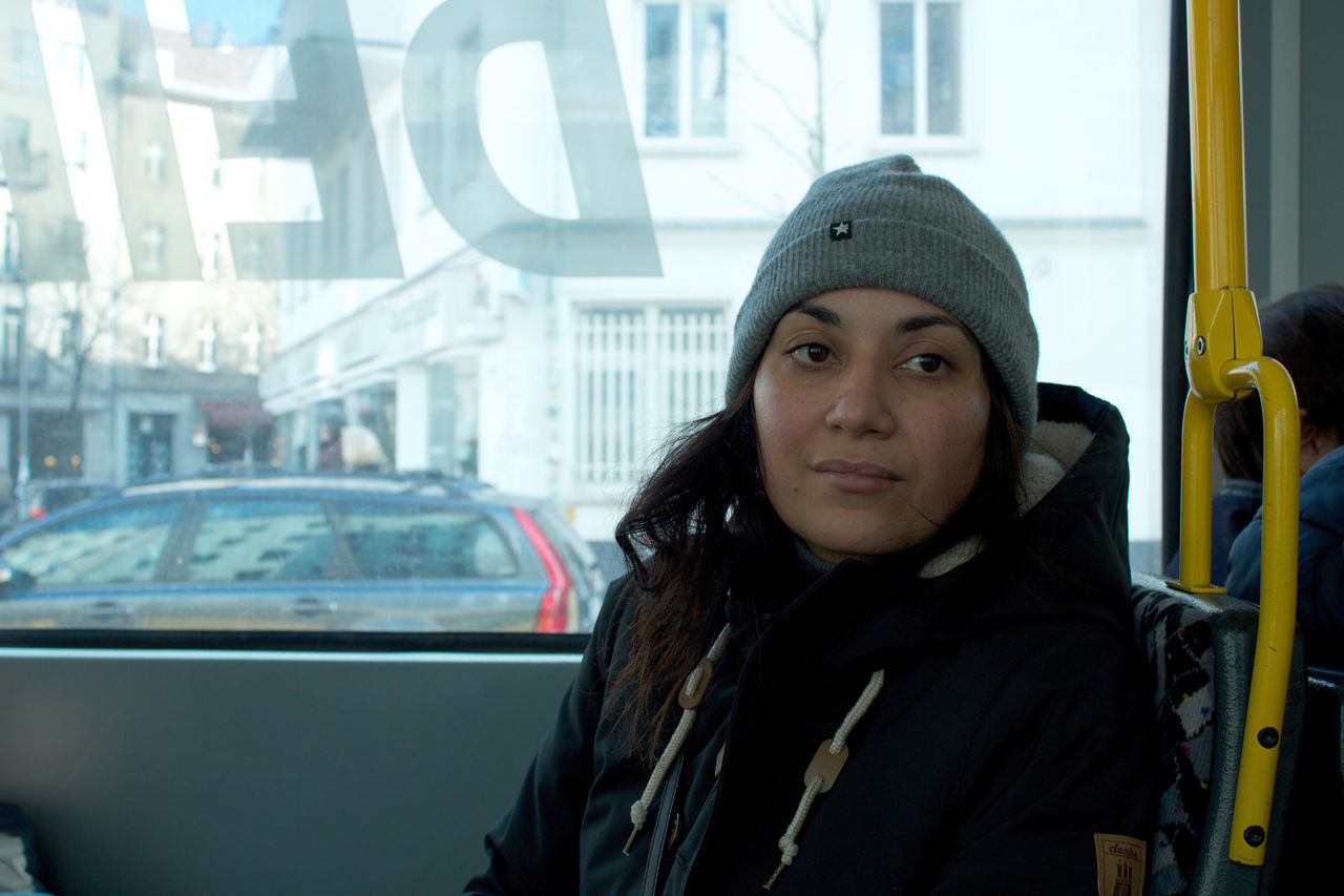 Woman in Public Transport. Adult Adults Only Car City Confidence  Day Focus On Foreground Front View Headshot Lifestyles Long Hair Looking At Camera One Person One Woman Only One Young Woman Only Only Women Overcoat People Portrait Real People Transportation Warm Clothing Women Young Adult Young Women