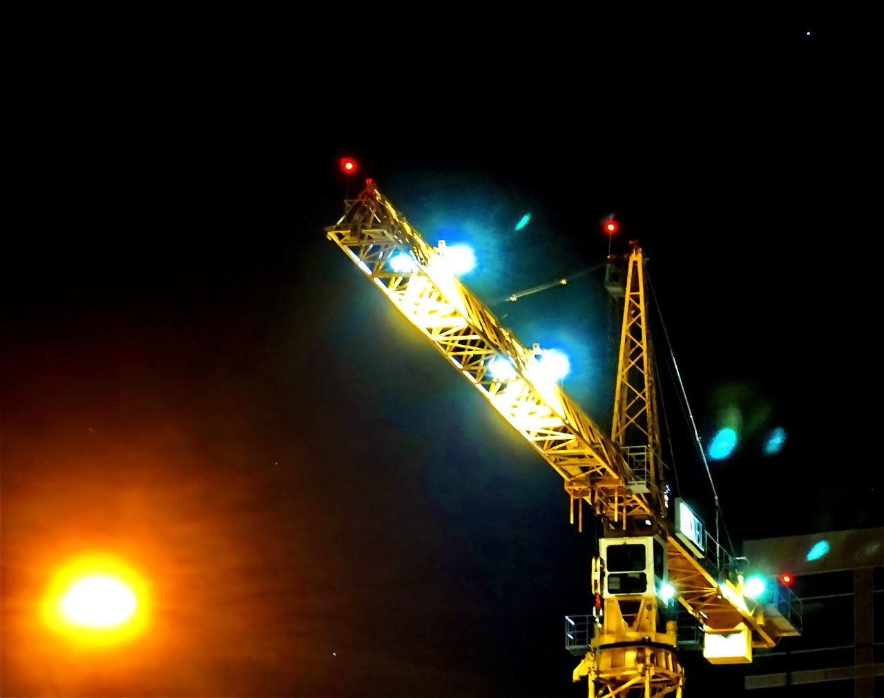 illuminated, night, transportation, low angle view, lighting equipment, lens flare, crane - construction machinery, mode of transport, no people, light beam, outdoors, freight transportation, street light, architecture, spotlight, clear sky, sky, city