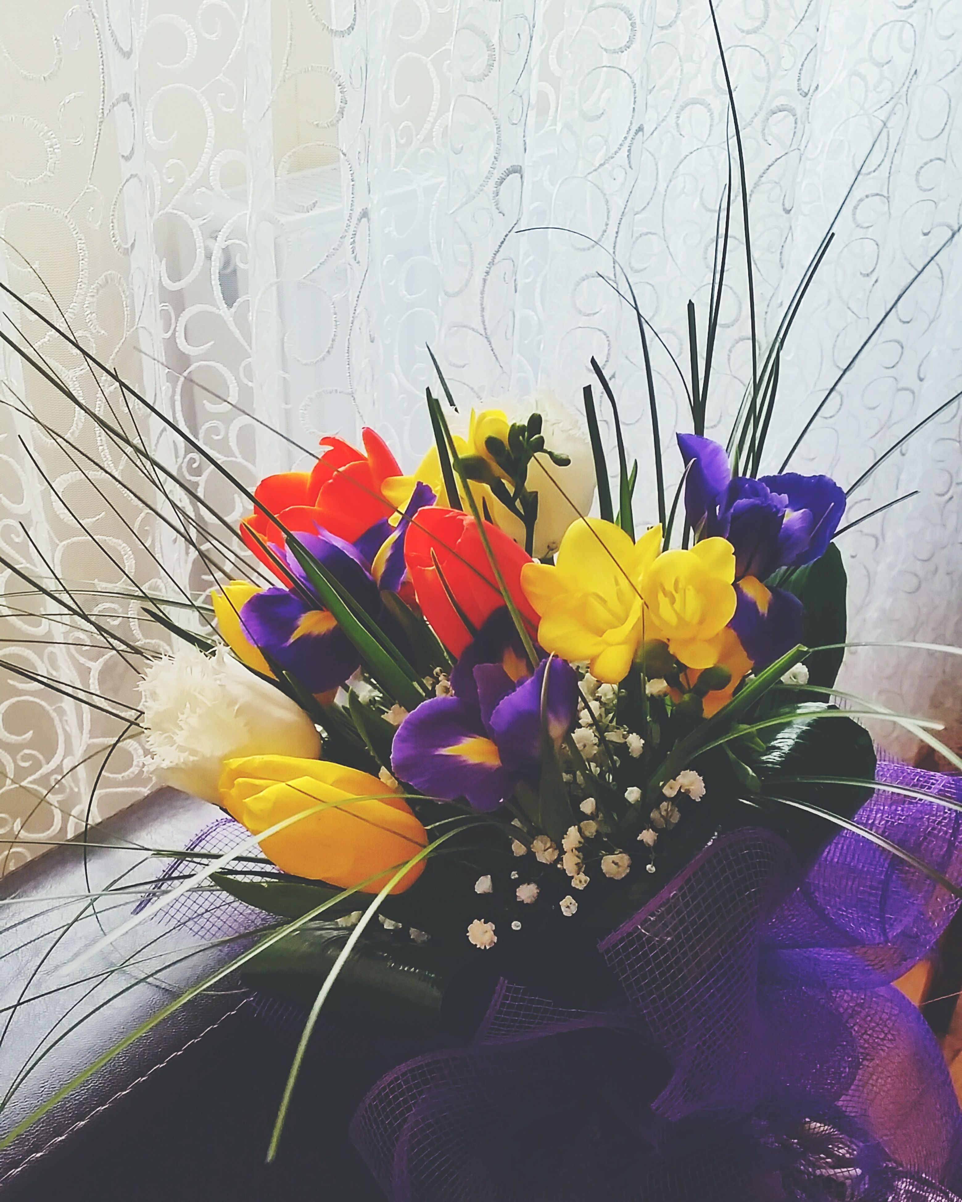 flower, fragility, petal, indoors, freshness, flower head, plant, vase, growth, wall - building feature, multi colored, close-up, yellow, home interior, decoration, blooming, nature, beauty in nature, stem, purple