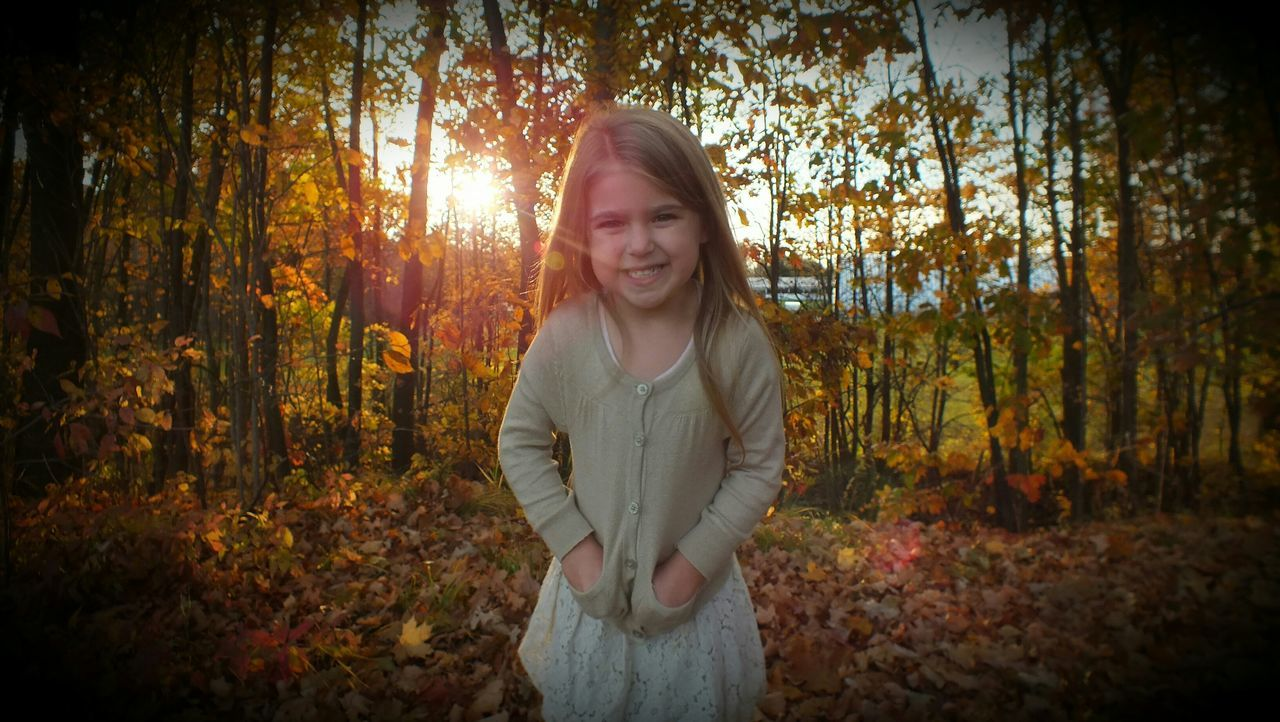 autumn, change, forest, tree, one person, nature, front view, real people, leaf, smiling, long hair, looking at camera, standing, outdoors, casual clothing, growth, happiness, leisure activity, young women, day, beautiful woman, young adult, tree trunk, portrait, lifestyles, beauty in nature, adult, people, adults only