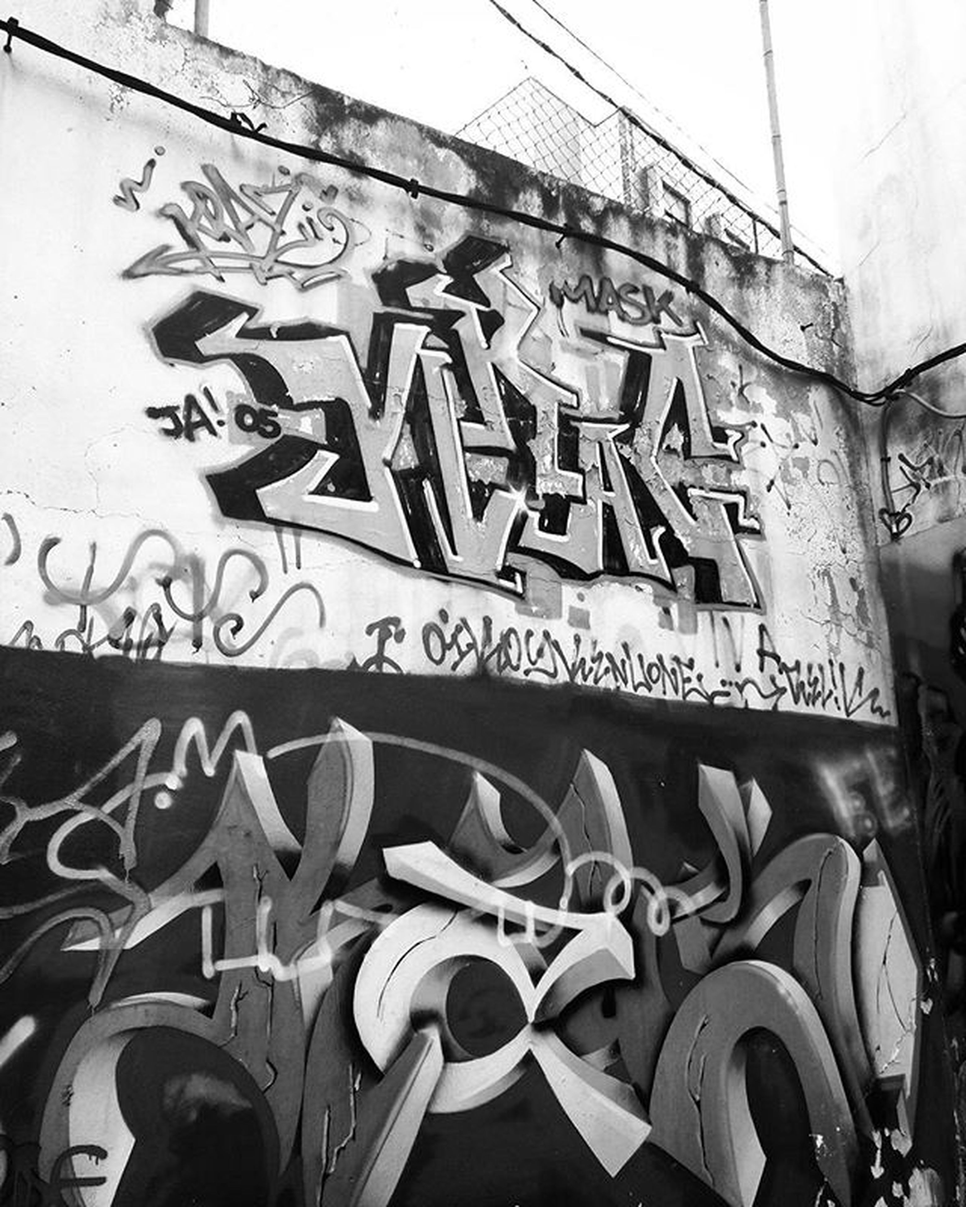 text, western script, graffiti, communication, low angle view, built structure, art, art and craft, architecture, creativity, capital letter, building exterior, wall - building feature, human representation, non-western script, information, sign, street art, day