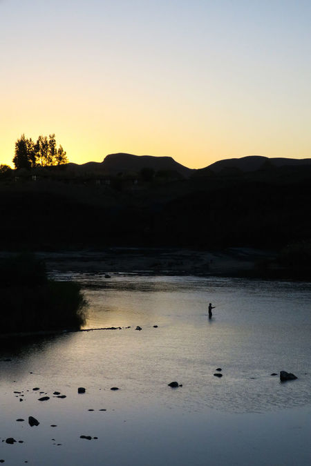 Fisherman casting into wide river as sun sets behind mountain backdrop Active Beauty In Nature Fishing Flyfishing  Lake Landscape Leisure Activity Mountain Nature Nature One Person Outdoor Outdoors Outdoors Photograpghy  Reflection River Riverside Scenics Silhouette Sunset Tranquil Scene Water Wilderness