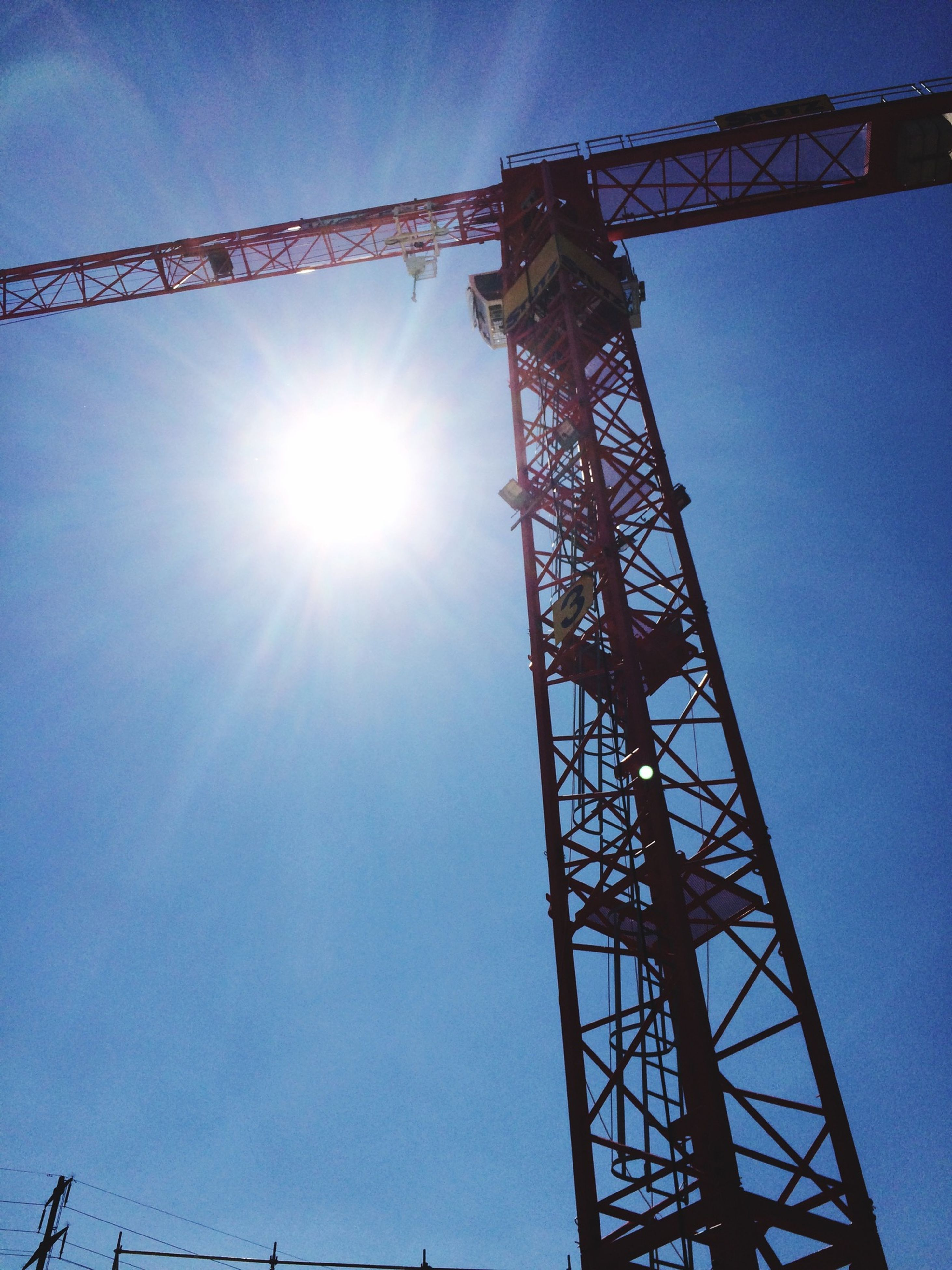 low angle view, sun, sunbeam, sunlight, built structure, lens flare, clear sky, sky, blue, crane - construction machinery, architecture, silhouette, tall - high, fuel and power generation, metal, construction site, day, outdoors, tower, no people
