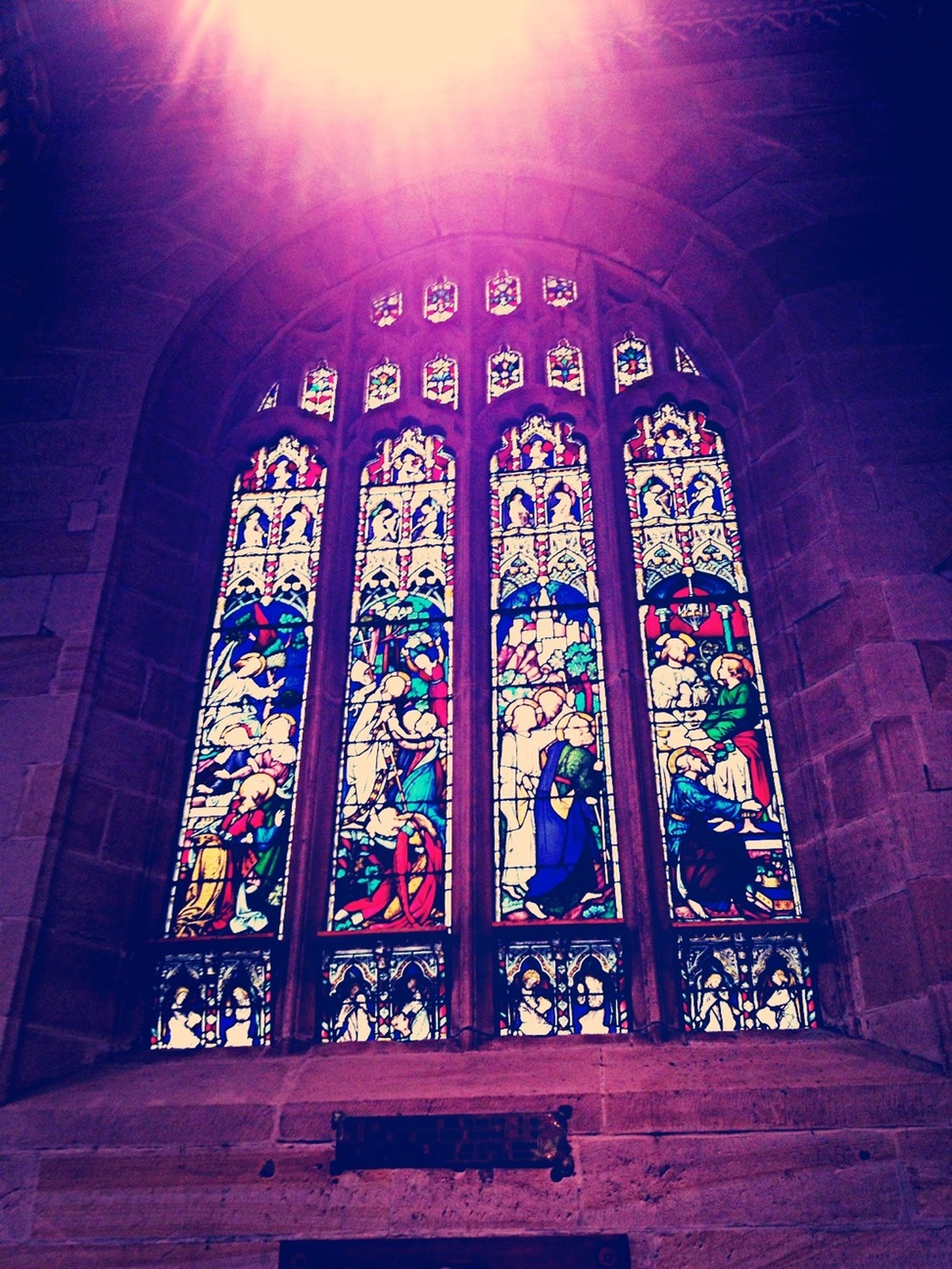 indoors, architecture, built structure, arch, stained glass, window, church, place of worship, religion, pattern, design, low angle view, spirituality, door, entrance, interior, sunlight, no people, ceiling