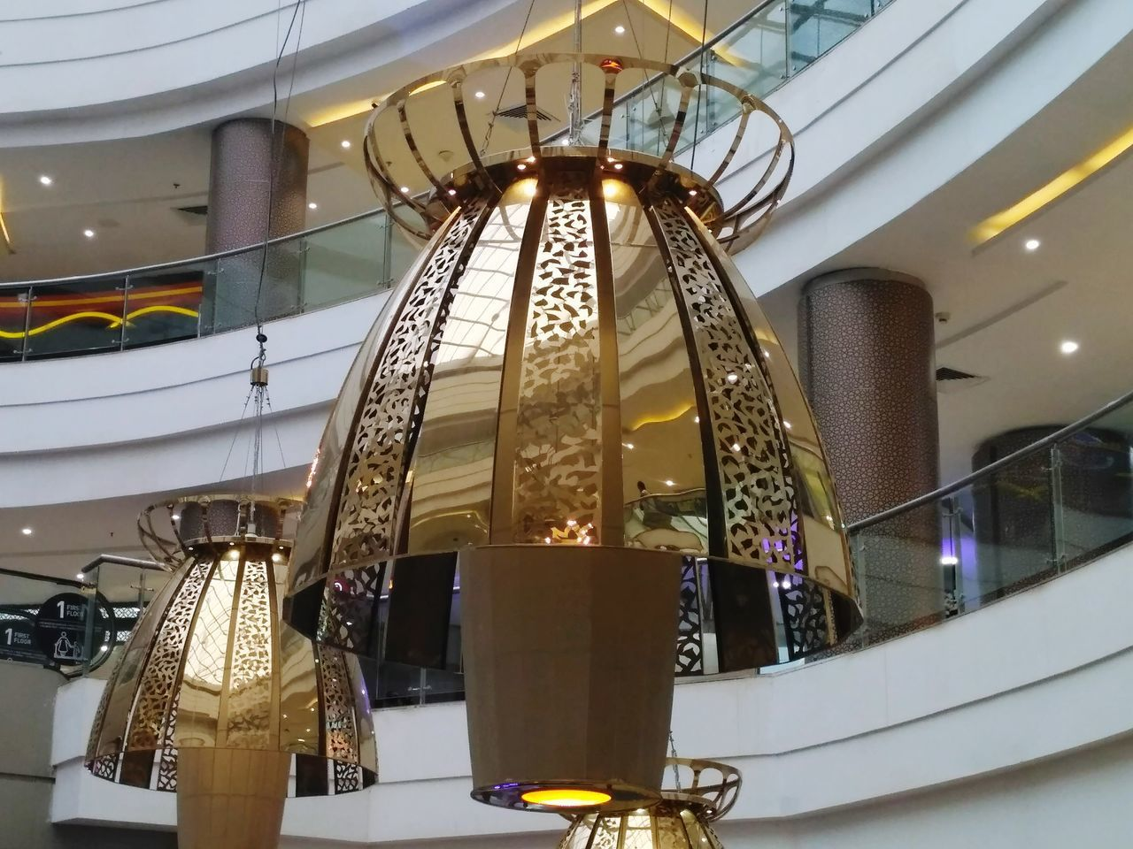 gold colored, low angle view, illuminated, indoors, hanging, architecture, no people, built structure, arts culture and entertainment, day