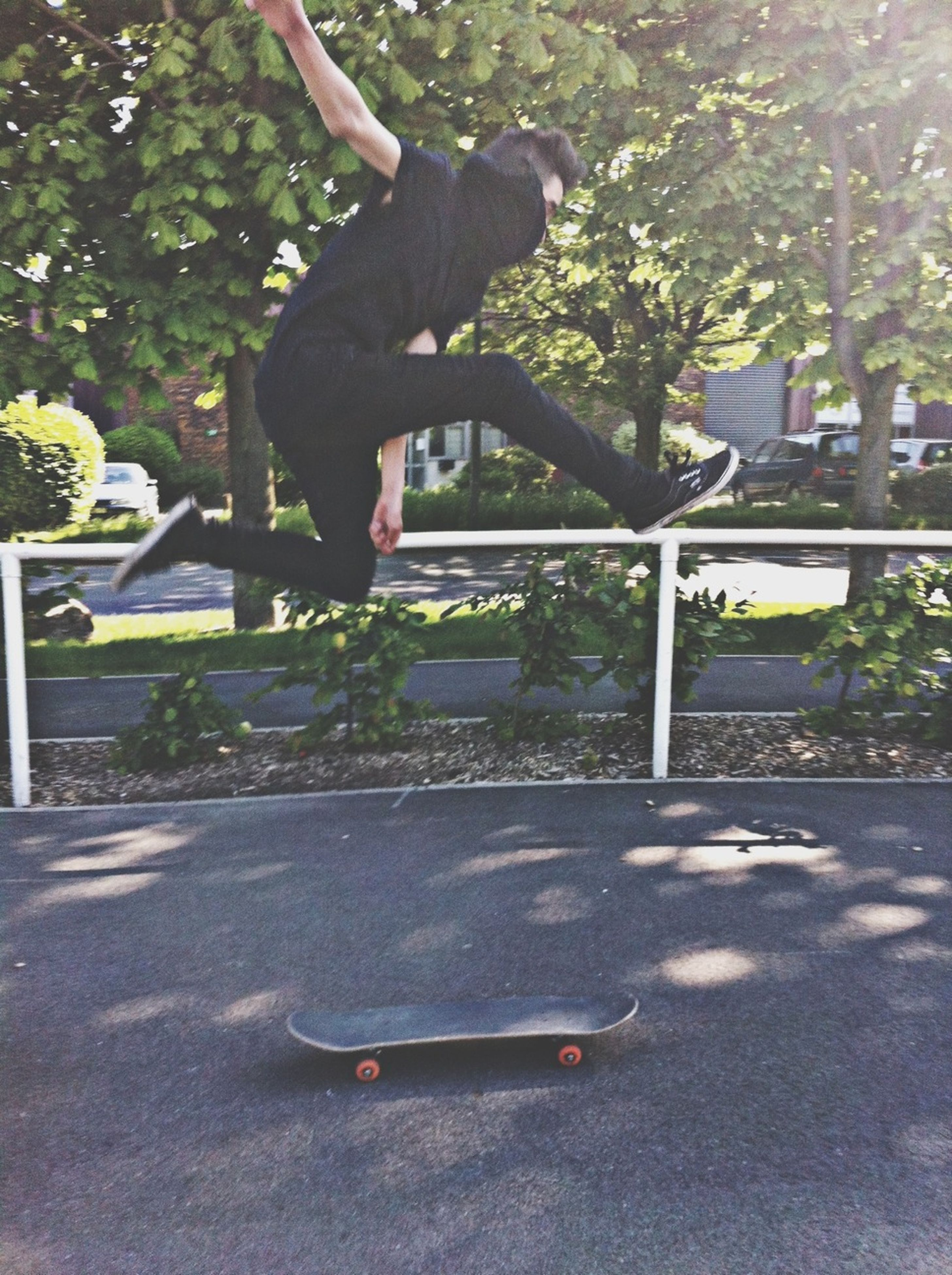 tree, lifestyles, full length, leisure activity, mid-air, jumping, street, low section, sport, men, skateboard, skill, road, sunlight, park - man made space, skateboarding, motion, outdoors