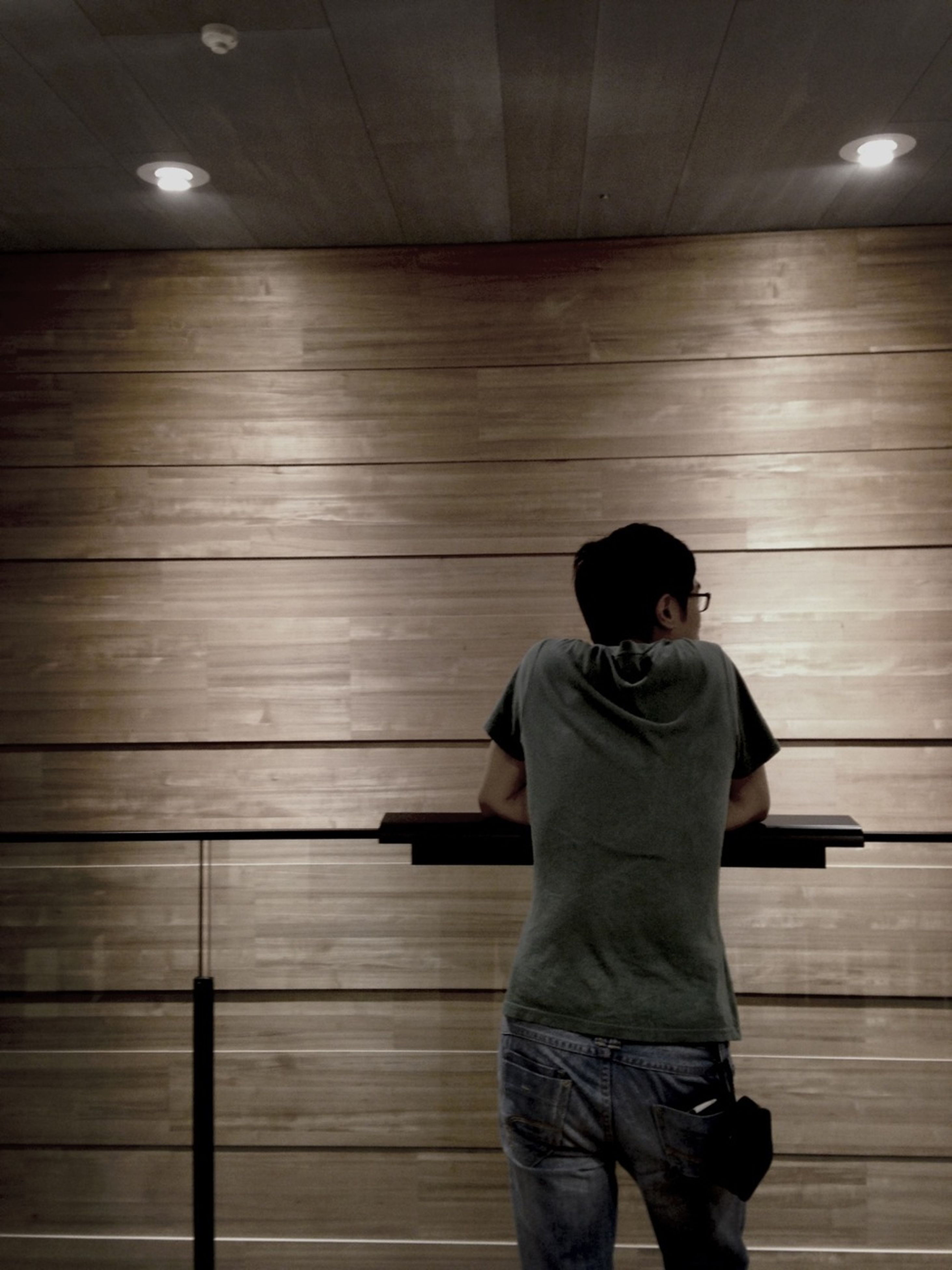 indoors, lifestyles, standing, leisure activity, casual clothing, rear view, three quarter length, men, technology, wood - material, full length, person, waist up, photographing, railing, photography themes, illuminated, connection