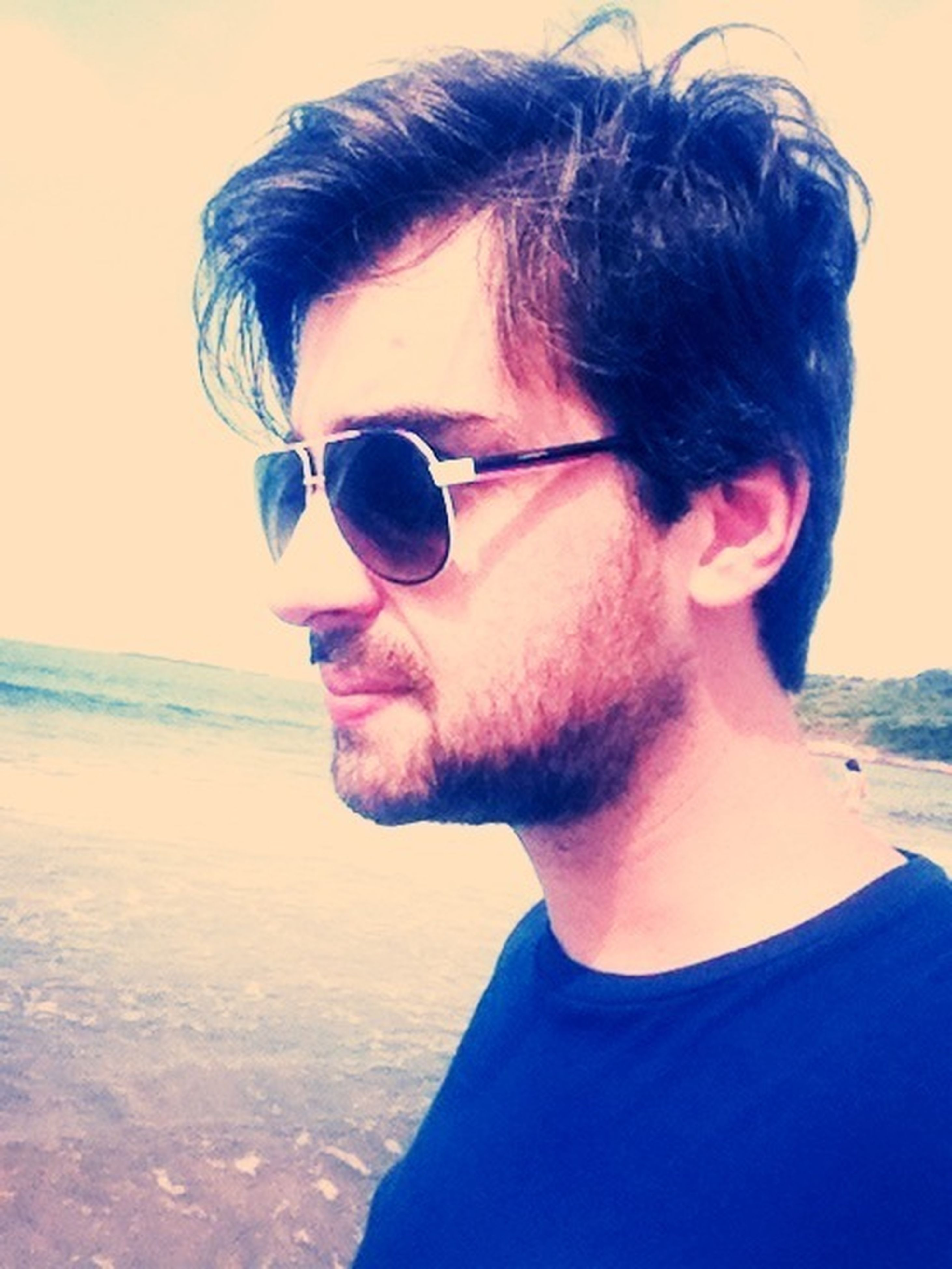 sunglasses, lifestyles, person, young adult, leisure activity, sea, beach, headshot, water, portrait, young men, vacations, looking at camera, sunlight, casual clothing, sky, front view