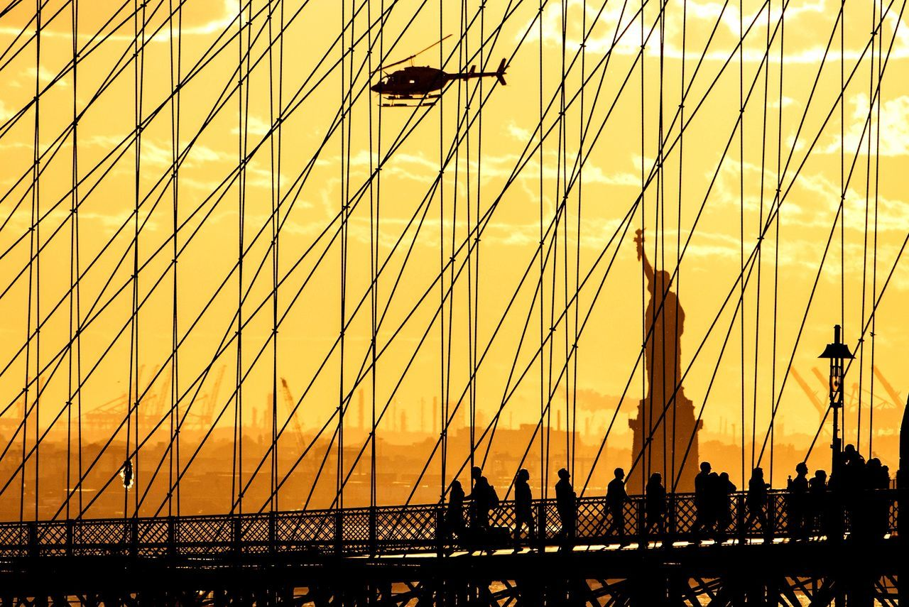 Statue of Liberty, Brooklyn Bridge and helicopter at sunset Sunset Silhouette Orange Color Tourism Sun City Sky Architecture Outdoors People Large Group Of People Cityscape Silouhettes Silouette River Suspension Bridge Travel Destinations Sunlight Built Structure Brooklyn Bridge  Bridge - Man Made StructureBrooklyn Bridge  New York New York City Brooklyn Bridge / New York