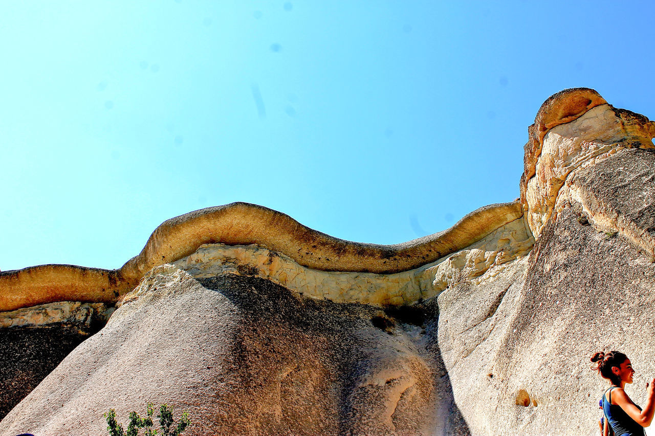 nature, rock - object, geology, rock formation, beauty in nature, day, physical geography, outdoors, clear sky, tranquility, scenics, tranquil scene, real people, blue, one person, rock hoodoo, arid climate, sky, animal themes, mammal, people