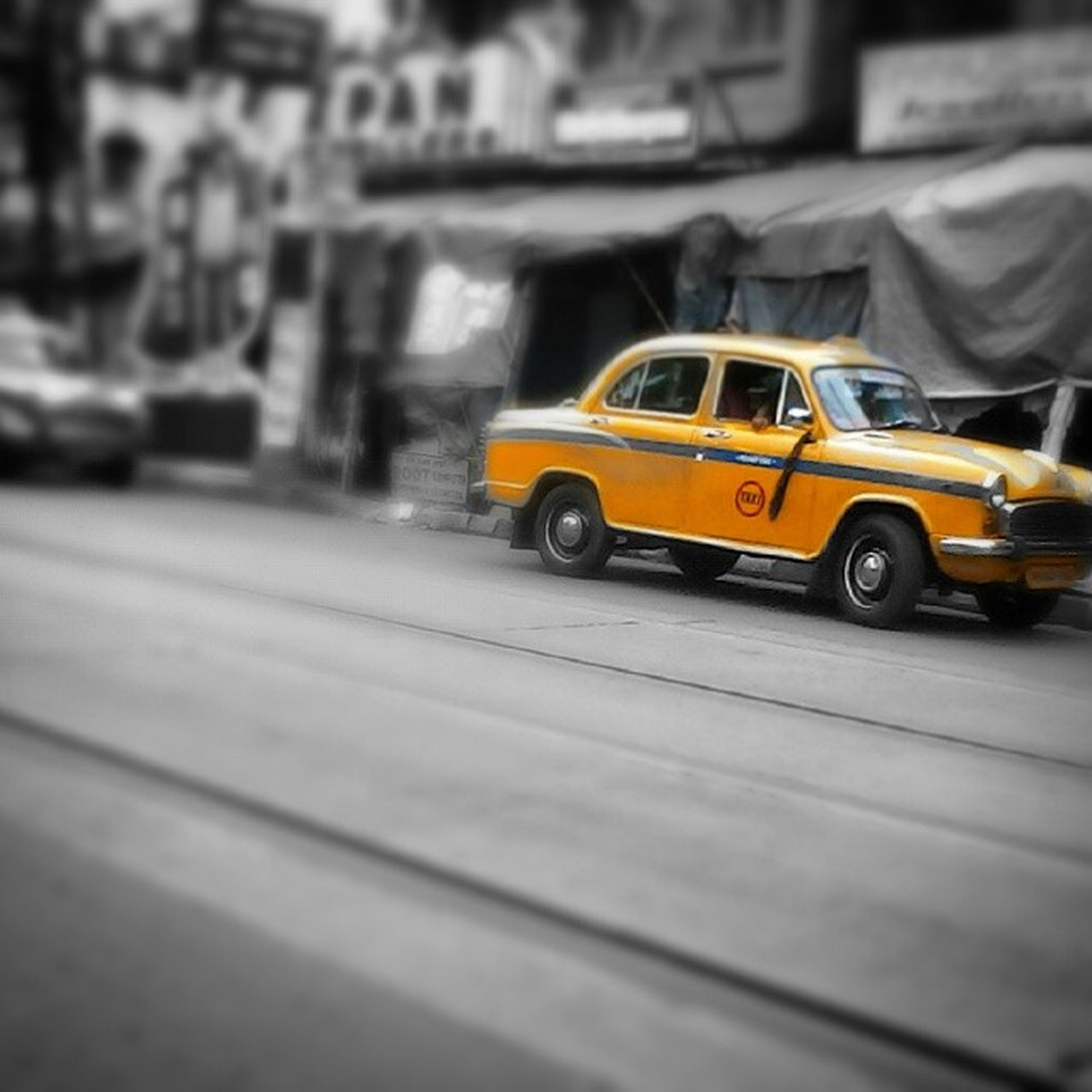 transportation, land vehicle, mode of transport, car, street, yellow, selective focus, road, focus on foreground, stationary, travel, on the move, outdoors, building exterior, vehicle, day, close-up, no people, parking, city
