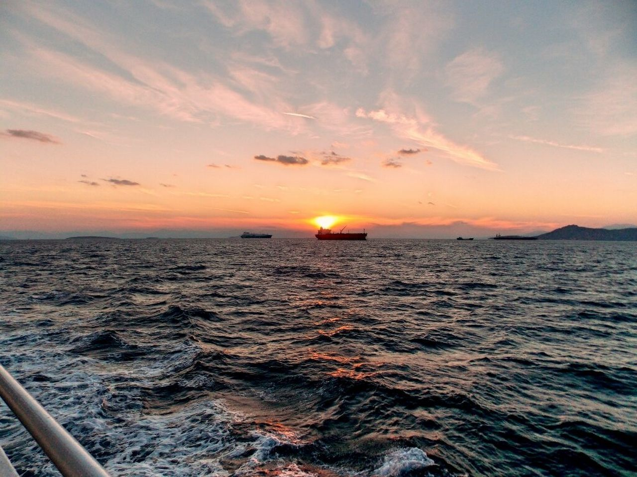 Cropped Image Of Boat Sailing In Sea Against Orange Sky