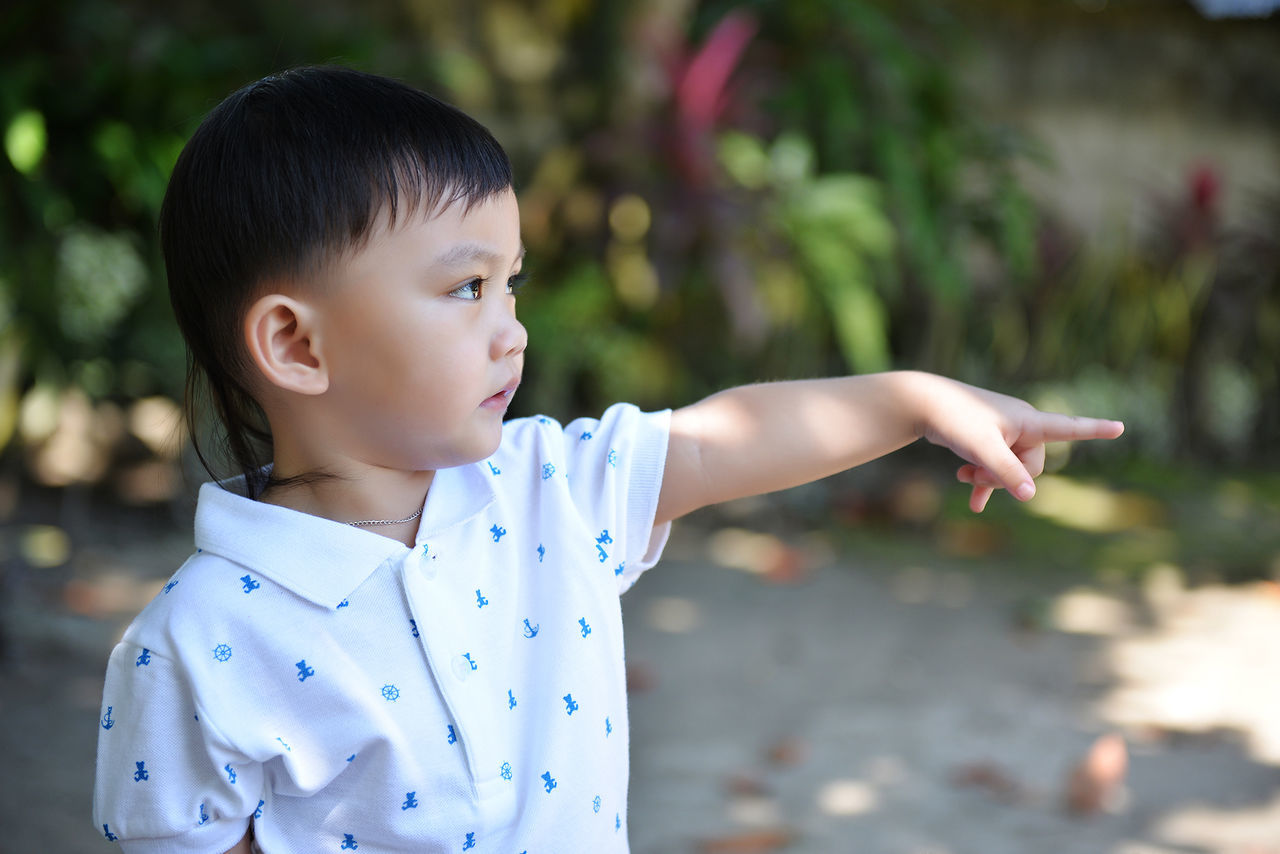 Close-Up Of Boy Gesturing While Standing On Field