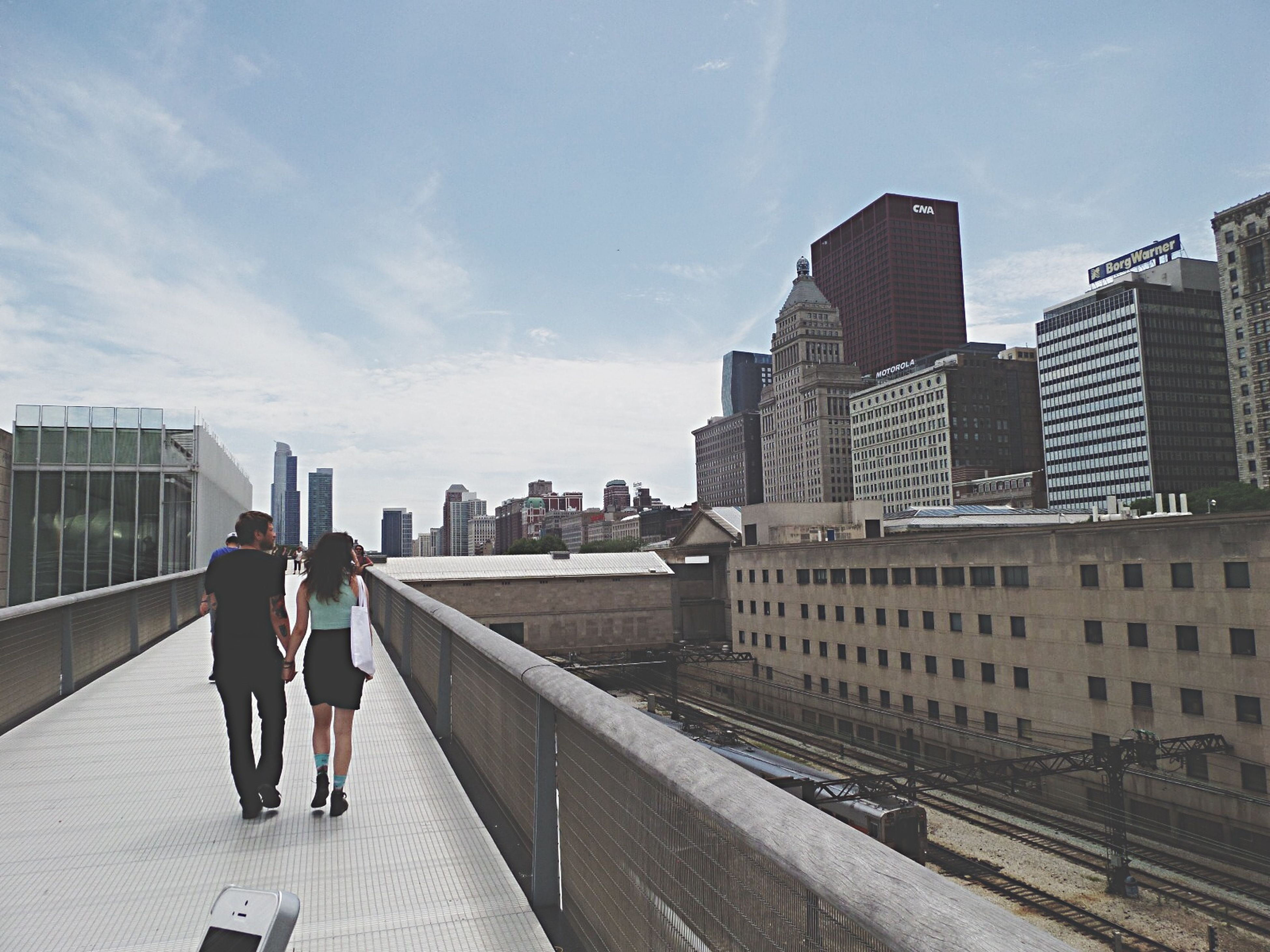 building exterior, architecture, built structure, full length, lifestyles, men, city, walking, sky, leisure activity, rear view, person, city life, railing, casual clothing, sunlight, cloud