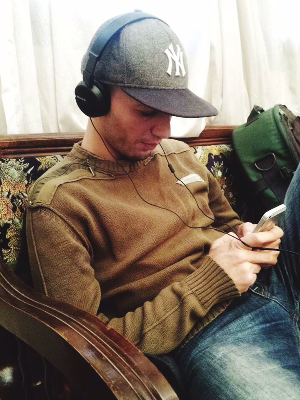 one person, real people, cap, casual clothing, indoors, holding, sitting, day, young adult, people