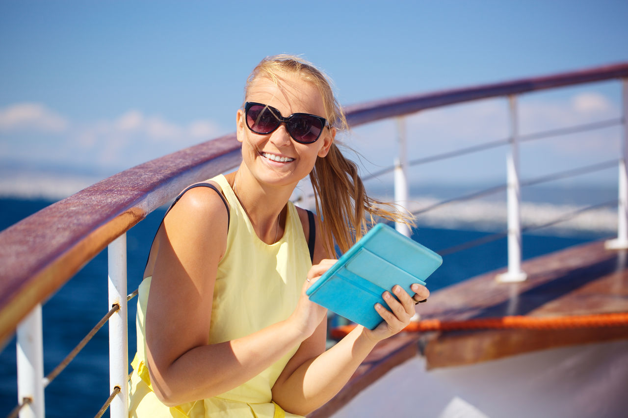 Portrait Of Happy Beautiful Woman Using Digital Tablet While Sailing In Boat During Sunny Day