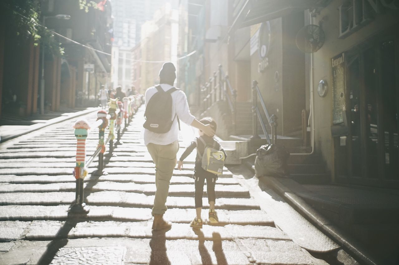Traveling Home For The Holidays City City Life Sunlight Young Adult City Street Walking Transportation Men People Outdoors Day Adult Built Structure Togetherness Building Exterior Friendship Adults Only Crowd