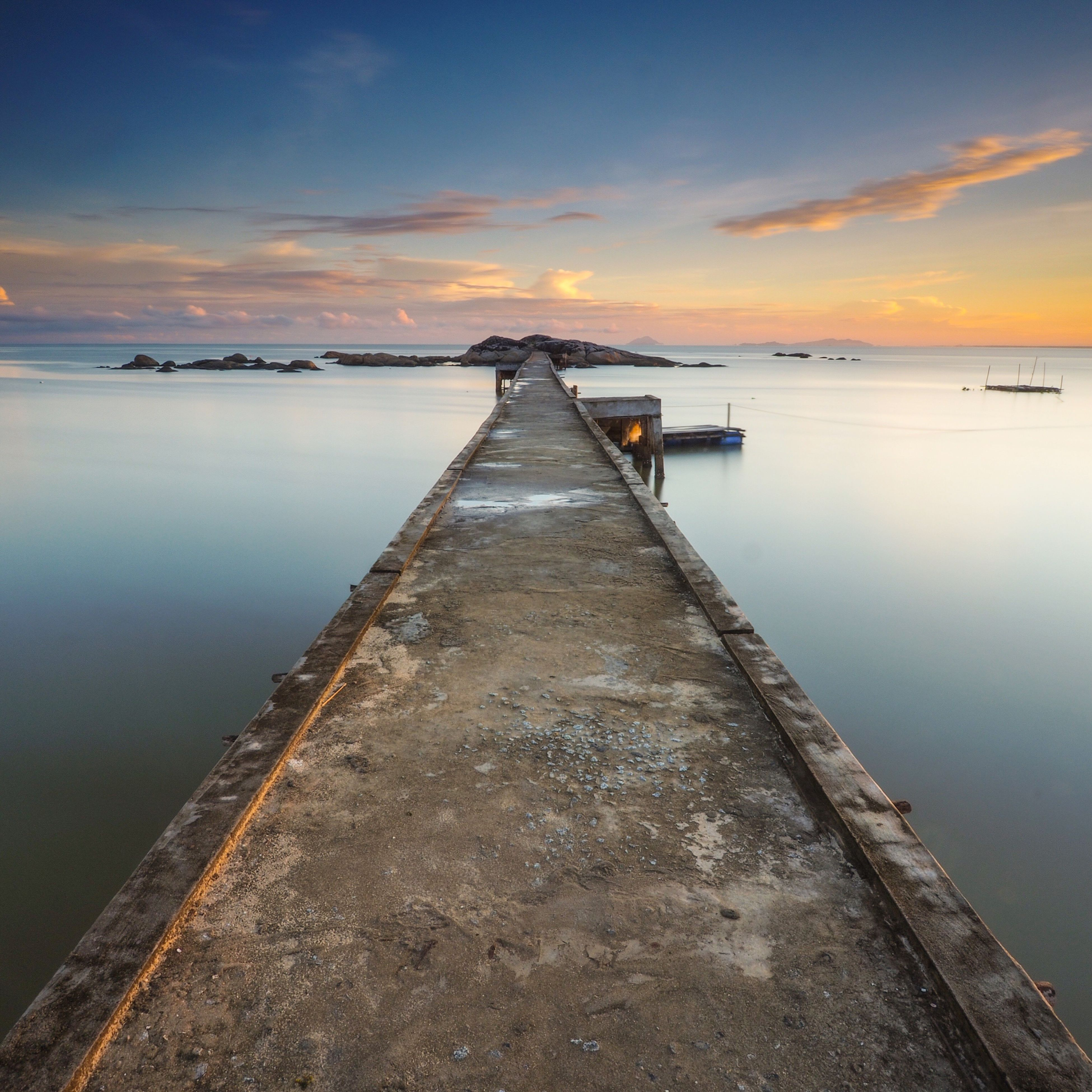 water, sunset, sea, sky, tranquility, tranquil scene, scenics, pier, beauty in nature, the way forward, nature, cloud - sky, idyllic, diminishing perspective, orange color, outdoors, no people, cloud, non-urban scene, cloudy, remote, ocean, vanishing point, weather, travel destinations