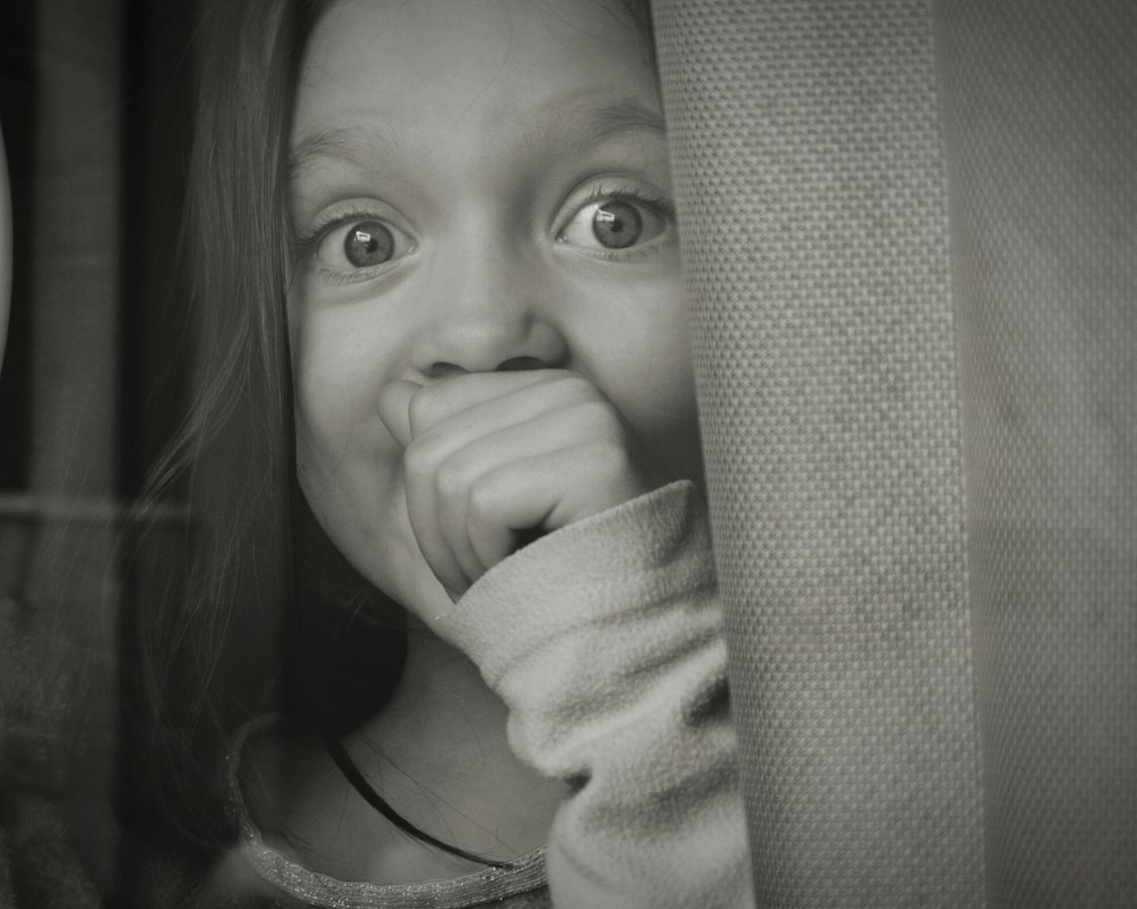Close-Up Portrait Of Surprised Girl With Hand Covering Mouth By Curtain