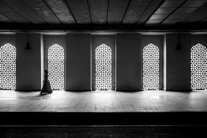 A woman walks past large arch windows in an indoor walkway Alone Arches Architecture Blackandwhite Built Structure Calmness Empty Space Hijab Indoors  Islamic Architecture Islamic Design Muslim Peaceful View Silhouette The Street Photographer - 2017 EyeEm Awards Walking Windows Woman