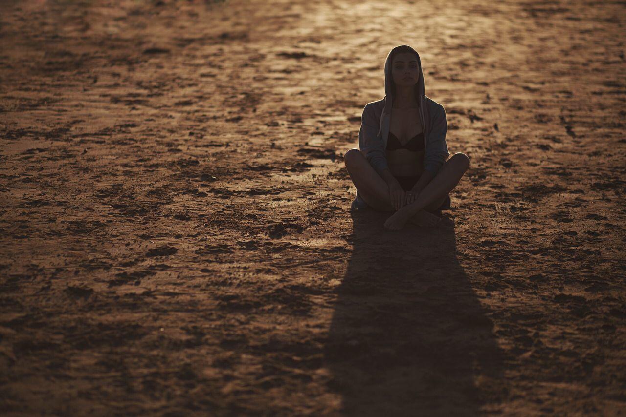 Woman Sitting On Ground At Sunset