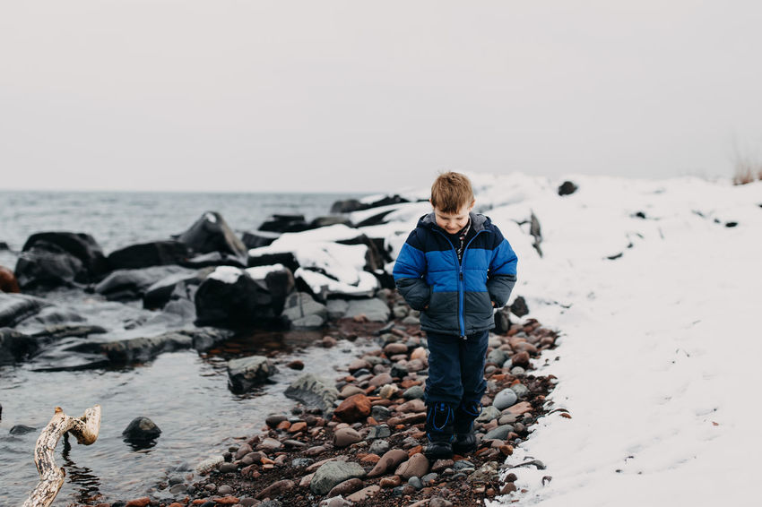 Spring Fling Kindergarten Lake Superior Looking Down North Shore Minnesota Rocky Beach Winter Adventure Blue Coat Boy Cold Temperature Collecting Rocks Day Lake Nature One Person Outdoors Overcast Day Playful