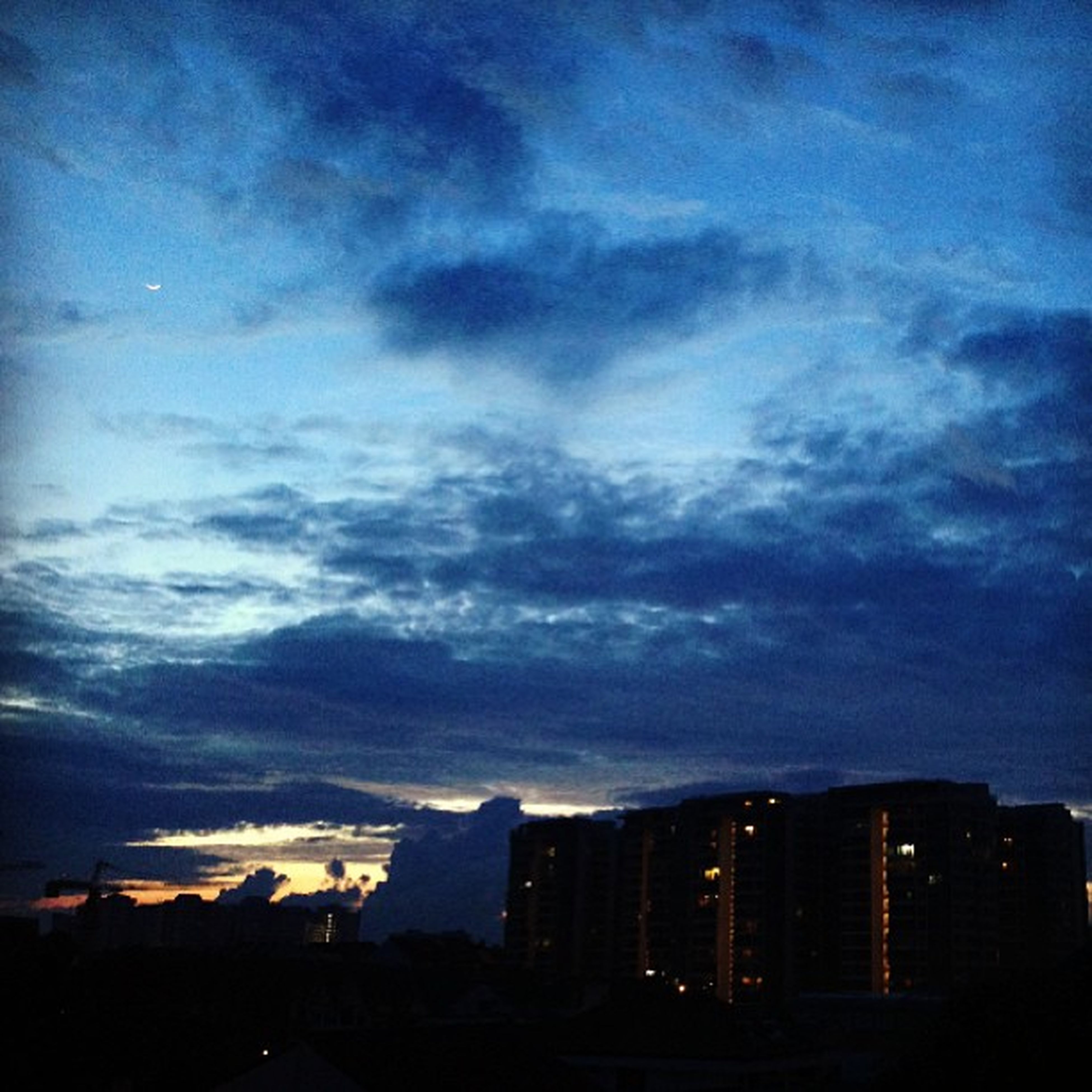 building exterior, architecture, built structure, sky, city, cloud - sky, cityscape, silhouette, cloudy, sunset, dusk, cloud, residential building, residential structure, weather, residential district, dramatic sky, outdoors, house, nature