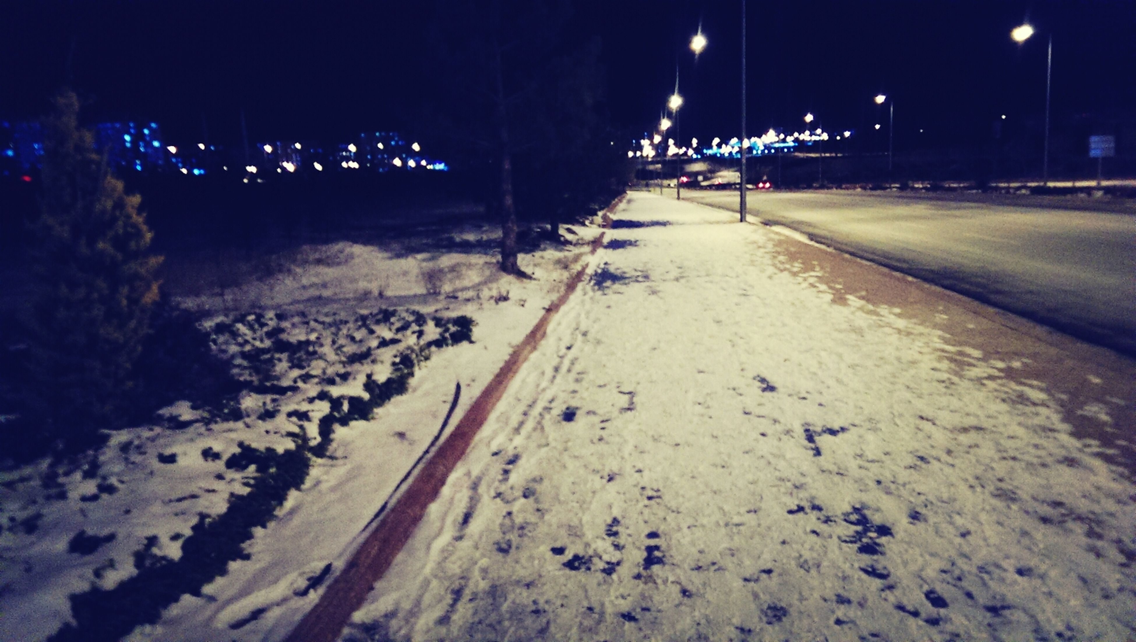 night, illuminated, the way forward, transportation, street light, road, diminishing perspective, snow, street, winter, vanishing point, lighting equipment, cold temperature, road marking, outdoors, incidental people, built structure, empty, architecture, building exterior