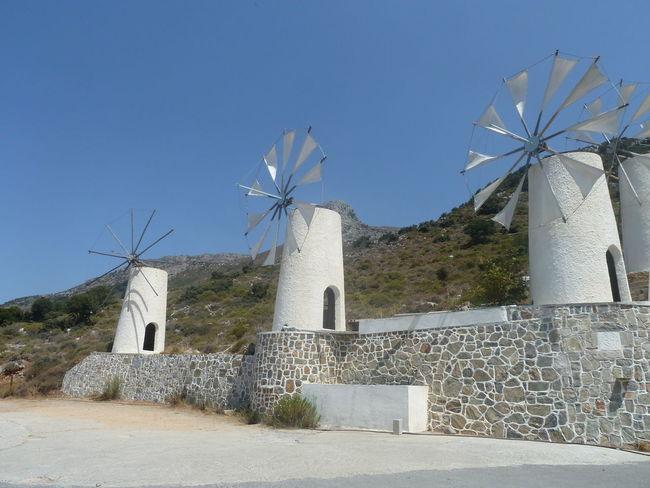 Alternative Energy Architecture Blue Built Structure Grass Hill Landscape Nature Non-urban Scene Outdoors Plant Sky Wind Power Windmill