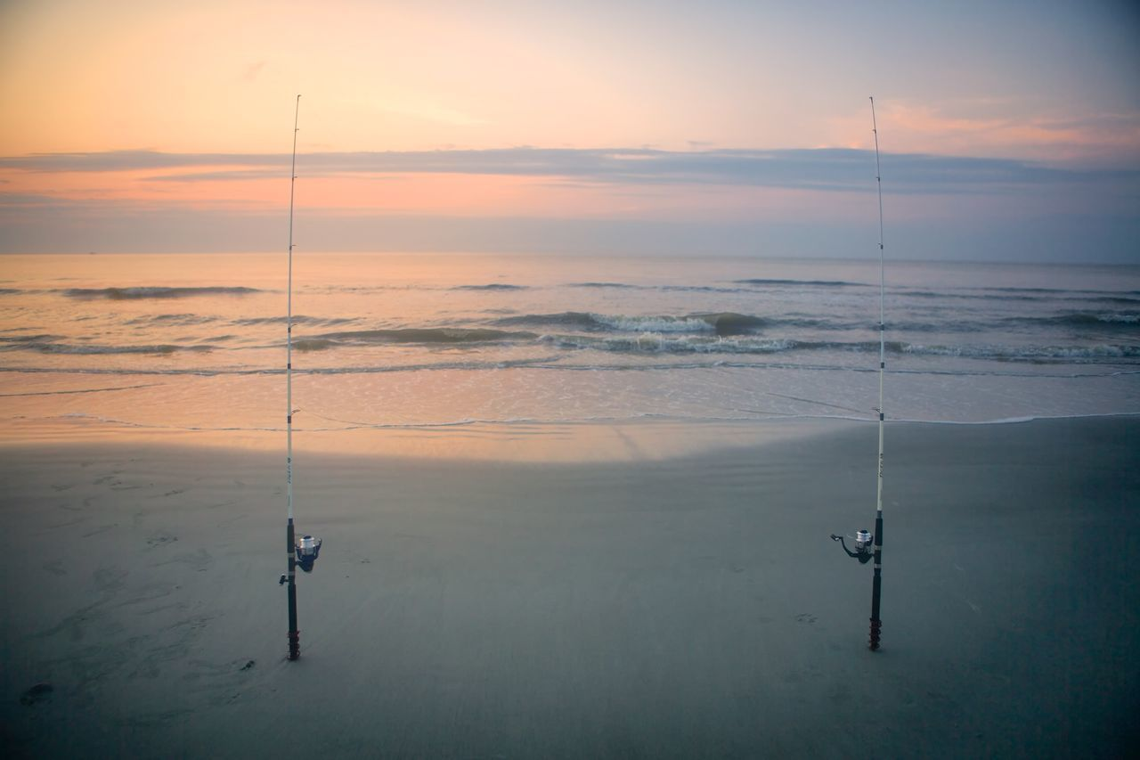Fishing Rods At Beach Against Sky During Sunset