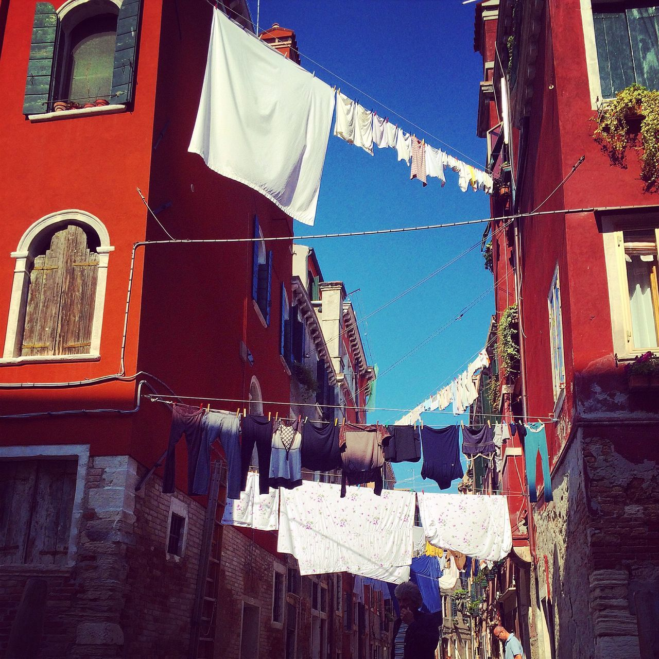 Low Angle View Of Clothes Lines Between Buildings Against Blue Sky