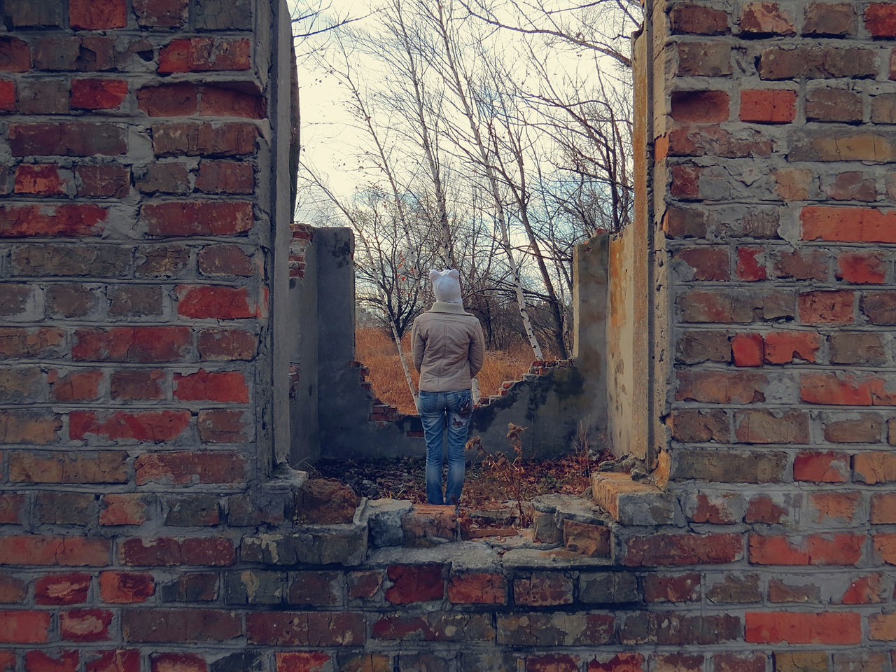 brick wall, rear view, real people, day, outdoors, bare tree, one person, architecture, full length, building exterior, people