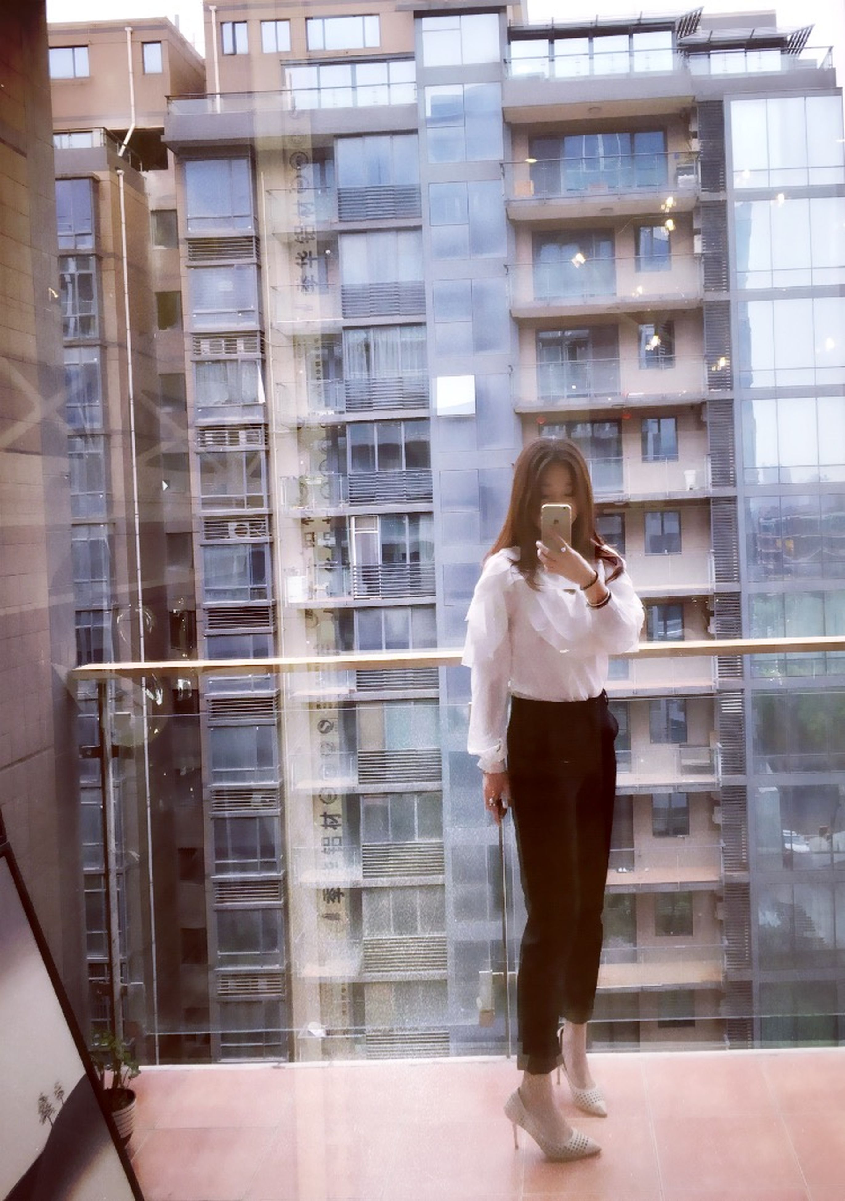 full length, architecture, built structure, building exterior, lifestyles, standing, casual clothing, rear view, young adult, leisure activity, building, young women, walking, three quarter length, person, city, side view, window