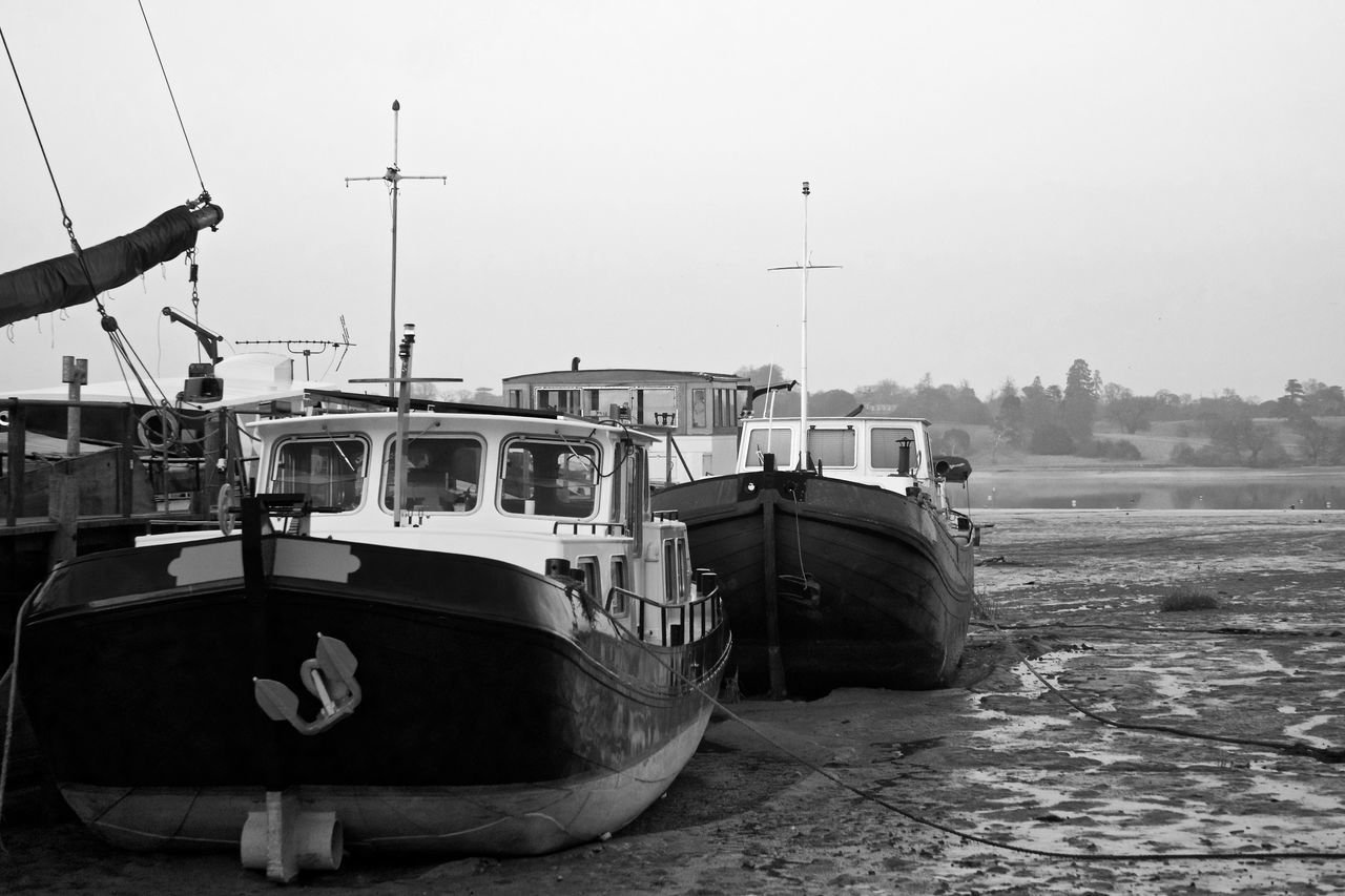 Old wooden boats turned into houseboats at Pin Mill, River Orwell, Suffolk, UK. Black And White Boat Clear Sky Day Estuary EyeEm Selects Harbor Low Tide Mast Mode Of Transport Monochrome Moored Mud Nautical Vessel No People Outdoors Pin Mill Transportation Water
