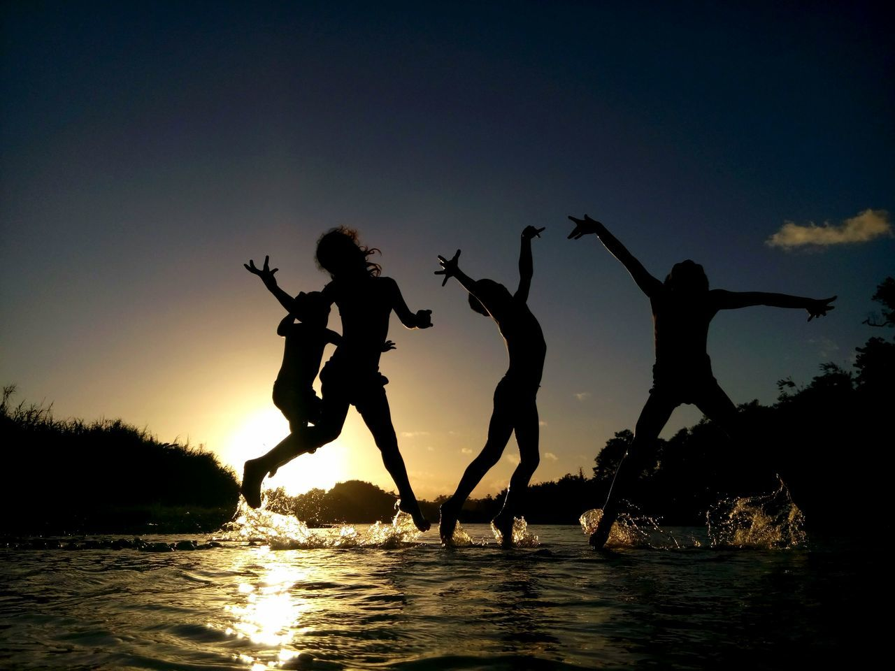 Silhouette Siblings Jumping Over River Against Sky During Sunset