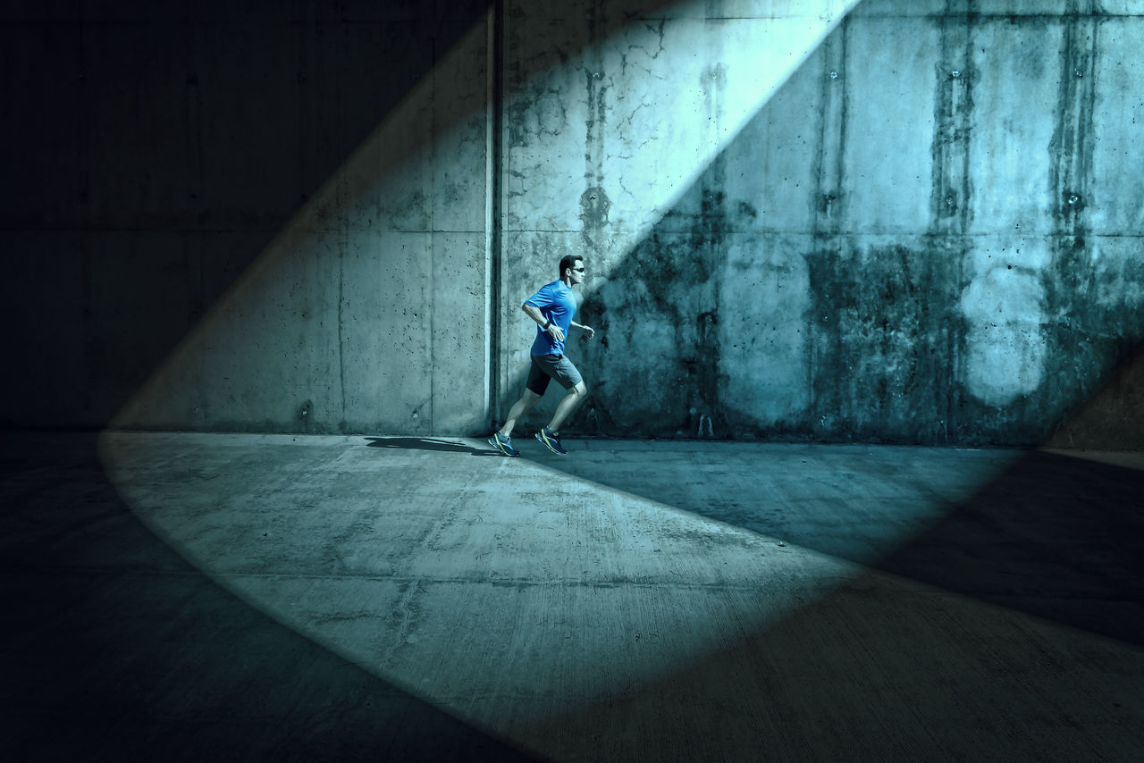 Runner under illuminated arcades Green Adult arcade blue day illuminated lifestyles men one person people real people runner shadow side view sport sports Sportsman