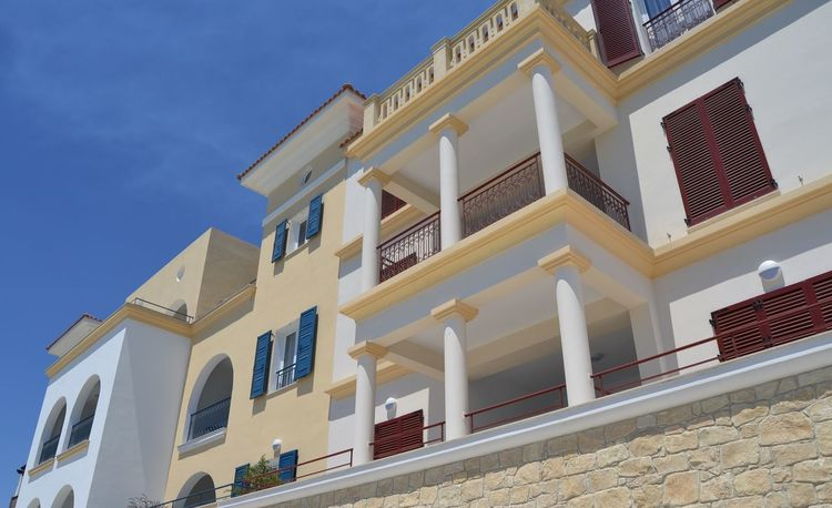 Modern Mediterranean style apartment building with blue and brown wooden shutters against whitewashed walls. Mediterranean  Modern Modern Architecture Wooden Shutters Apartment Arched Windows Architecture Balcony Blue Blue Shutters Building Exterior Built Structure City Clear Sky Day House Low Angle View Luxury Apartments No People Outdoors Residential Building Sky Whitewashed Window