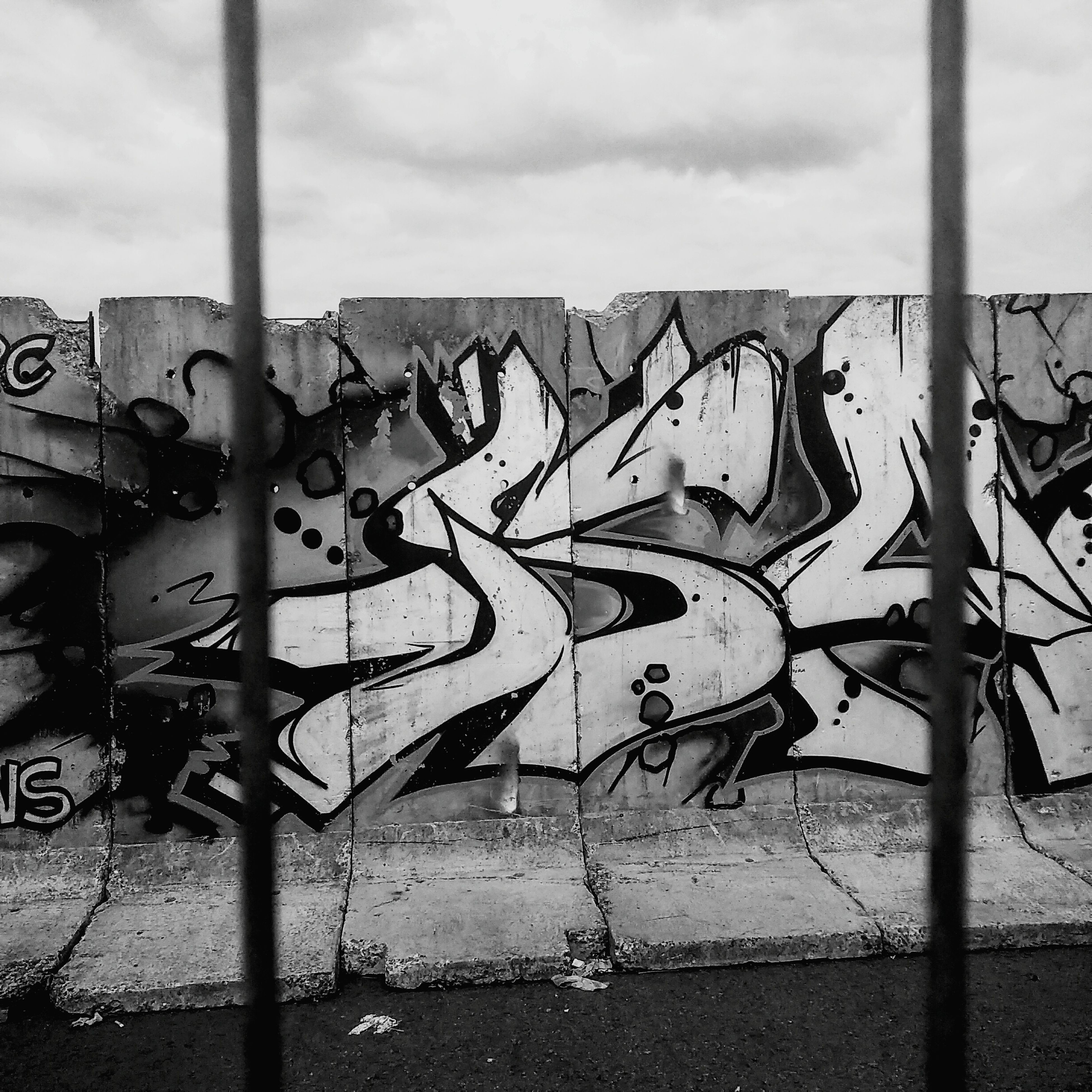 creativity, wall - building feature, art, metal, fence, graffiti, art and craft, protection, safety, sky, security, day, chainlink fence, outdoors, no people, built structure, metallic, sunlight, close-up, architecture