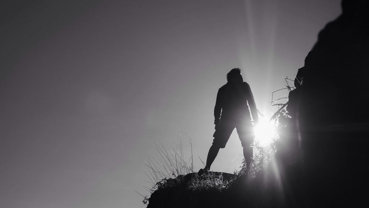 silhouette, real people, sun, low angle view, outdoors, illuminated, full length, nature, men, adventure, one person, light beam, beauty in nature, sky, people