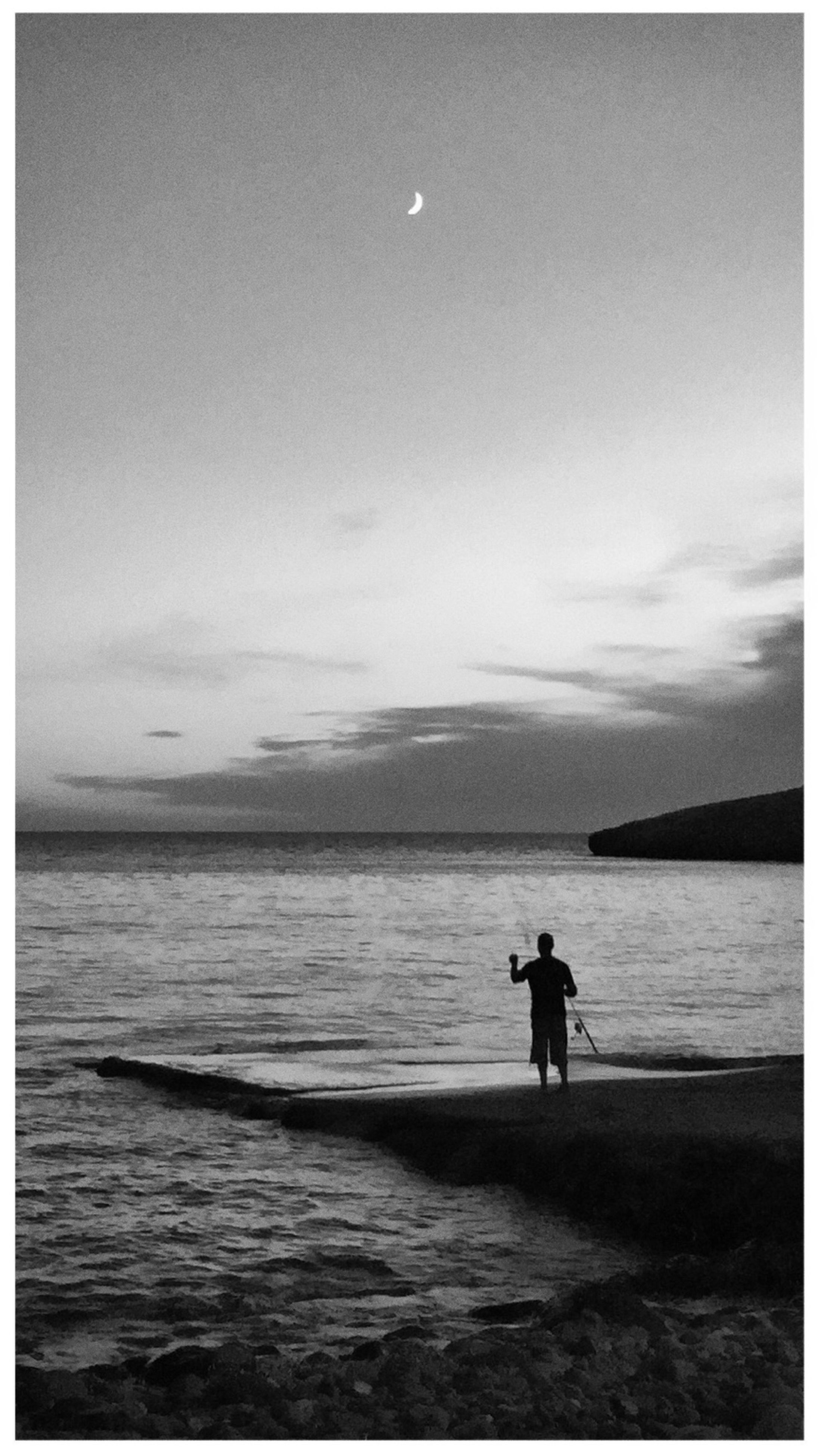sea, water, transfer print, lifestyles, beach, leisure activity, sky, tranquil scene, full length, horizon over water, scenics, tranquility, auto post production filter, men, shore, rear view, beauty in nature, standing