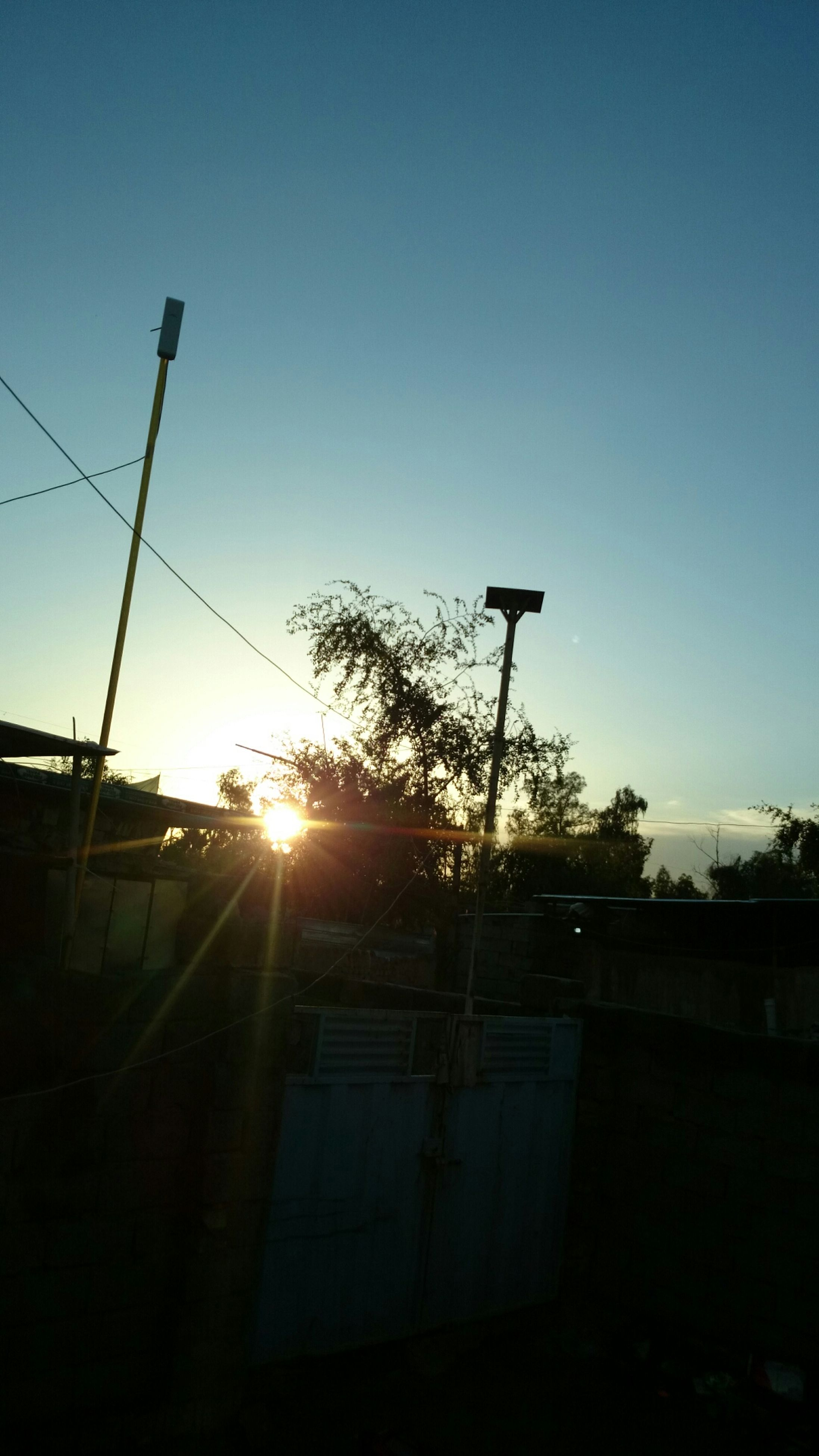 sun, building exterior, built structure, clear sky, architecture, silhouette, sunlight, sunset, tree, street light, low angle view, house, sunbeam, copy space, lens flare, sky, nature, no people, residential structure, outdoors