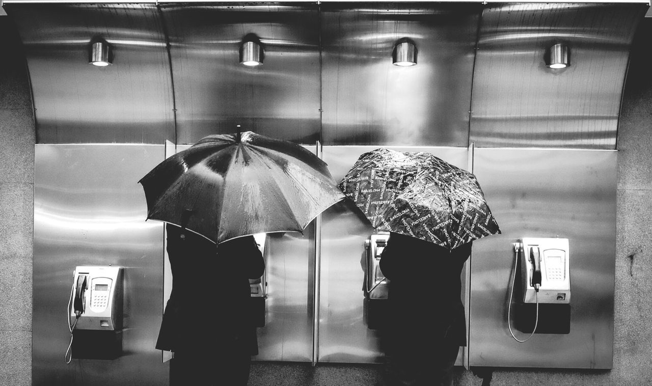 Rear view of two people with umbrellas at public booth