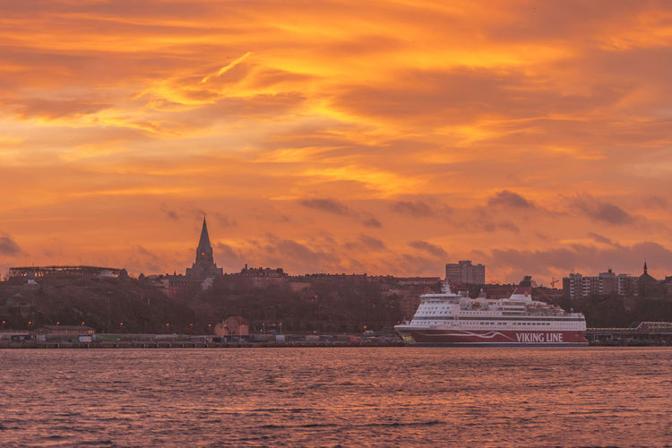 STOCKHOLM, SWEDEN - DEC 30, 2016: Cinderella from the Viking Line company embarking to the port in Stockholm. With a great orange evening sky. Architecture Church City Cityscape Cityscape Dusk Gabriella Landscape No People Outdoors Scenics Sky Stockholm Sunset Sweden Travel Travel Destinations Urban Skyline Water