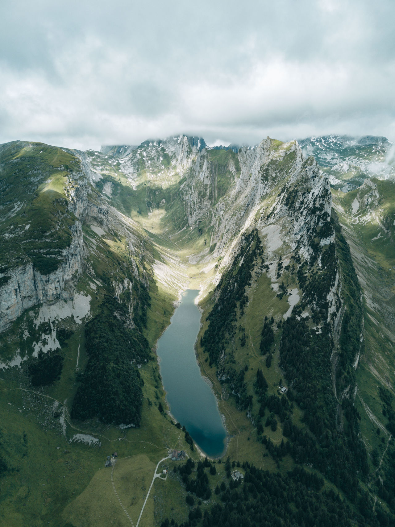 Panoramic view of a mountain range with a long lake and clouded sky Beauty In Nature Cloud - Sky Day Landscape Mountain Nature No People Outdoors Physical Geography Scenics Sky Tranquility Tree Water
