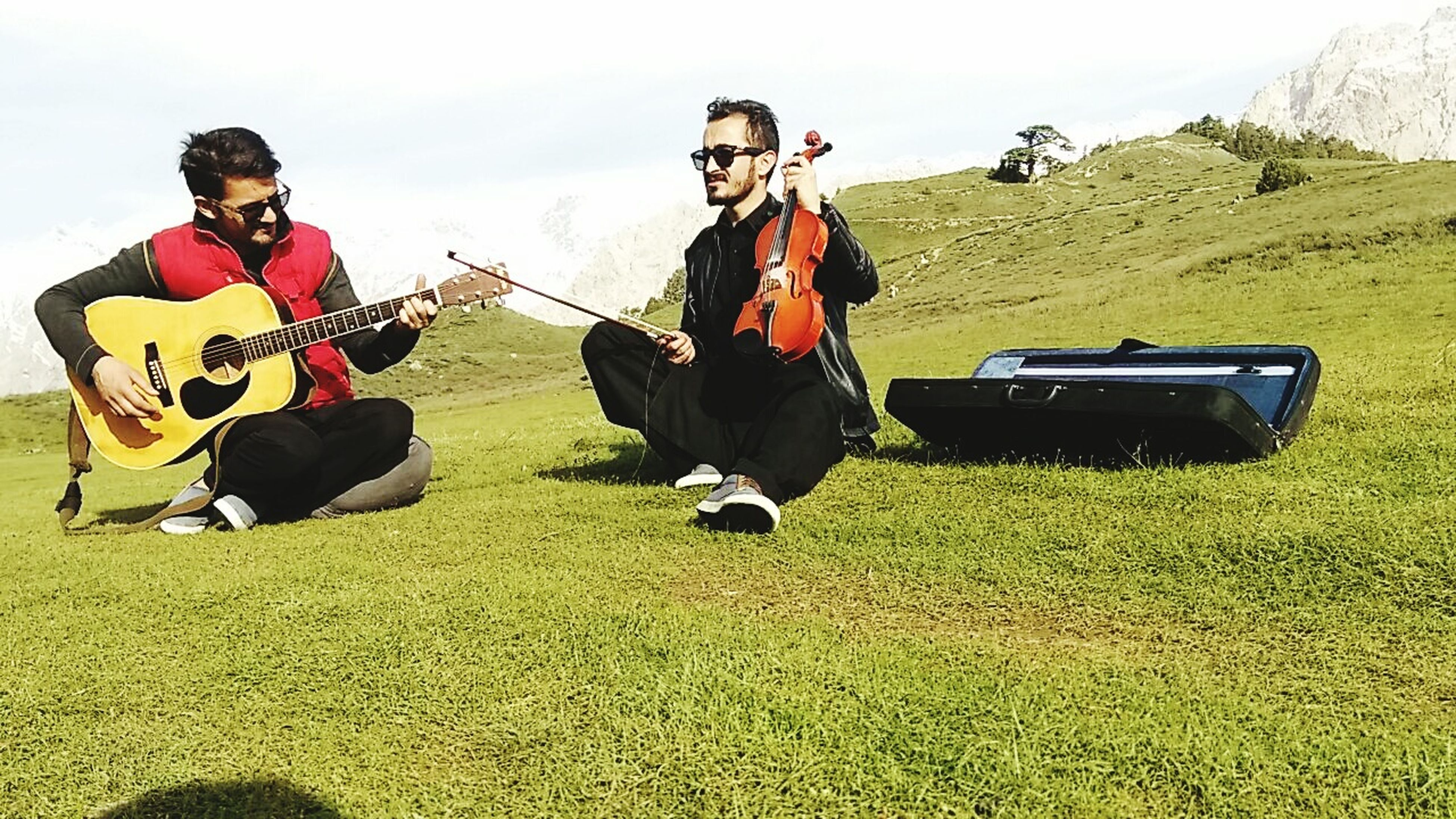 playing, guitar, music, sitting, enjoyment, young adult, musical instrument, plucking an instrument, adults only, outdoors, adult, full length, fun, people, guitarist, only men, leisure activity, musician, men, day, togetherness, friendship, sky