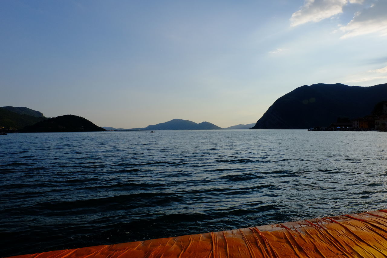 Beauty In Nature Blue Calm Coastline Floating Piers Fujifilm Idyllic Lago D'Iseo Majestic Mountain Mountain Range Nature Outdoors Physical Geography Remote Rippled Rock Formation Scenics Sea Sky Sunset Tranquil Scene Tranquility Travel Destinations Water