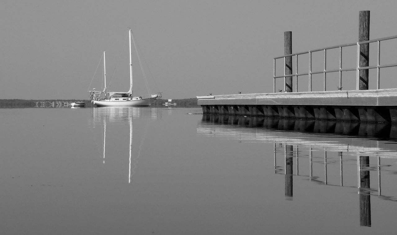 Sailboat Nautical Vessel Transportation Boat Dock Riverside Water Clear Sky Treeline Tranquility From A Distance Black And White Photography