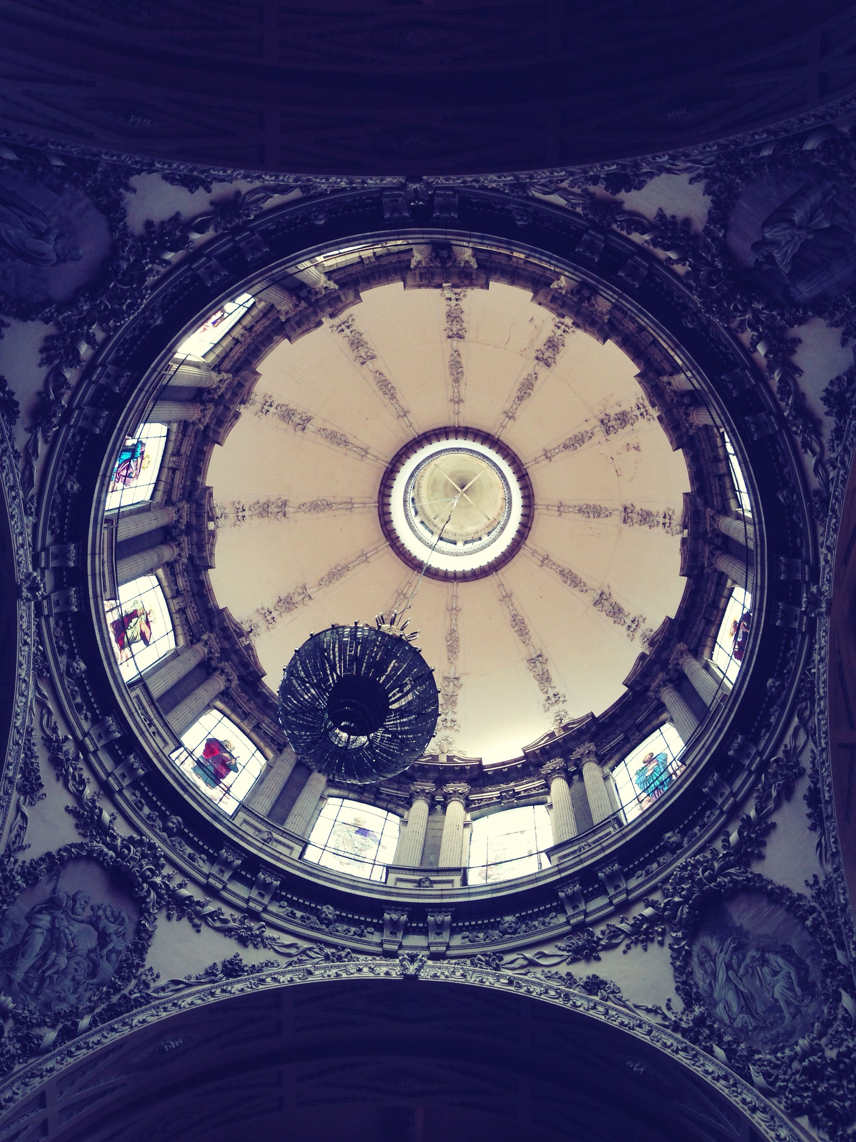 indoors, clock, circle, time, architecture, built structure, low angle view, ceiling, directly below, clock face, geometric shape, design, pattern, ornate, roman numeral, no people, architectural feature, history, skylight, church