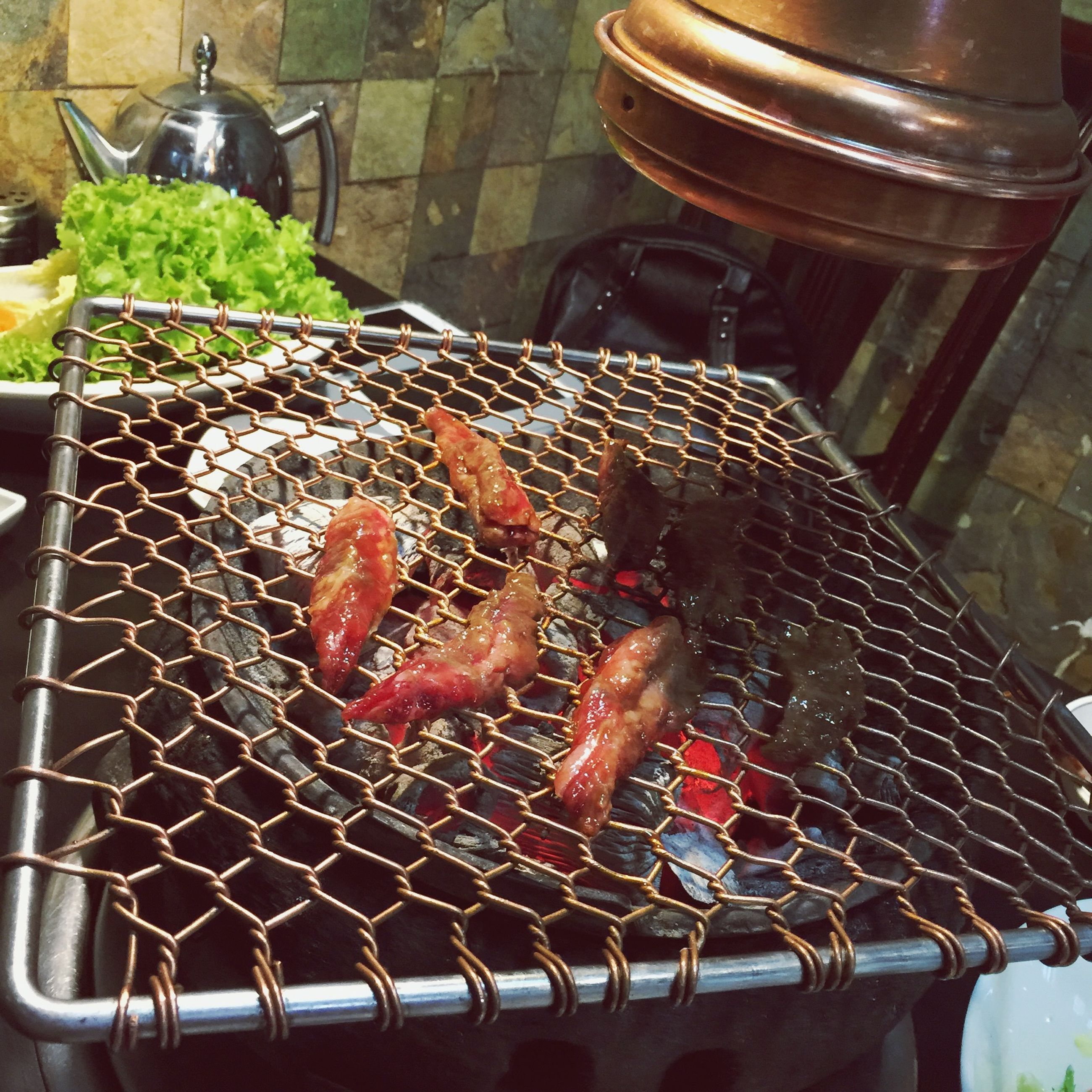 animal themes, indoors, food and drink, food, high angle view, close-up, metal, one animal, heat - temperature, fish, no people, preparation, seafood, barbecue grill, container, freshness, cooking, healthy eating, day, fire - natural phenomenon